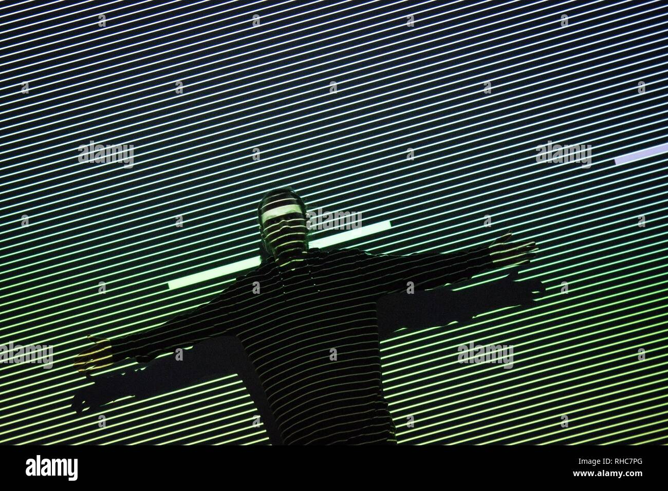 A visitor seen performing with the lights and effect of the Multimedia project Data Flux (12 XGA version) by Japanese artist Ryoji Ikeda at the Onassis Cultural Center in Athens. The Japanese artist presents an installation which challenges the limits of human perception and digital technology. With the precision of a metronome, twelve parallel video projectors synchronize with a minimalist electronic composition, turning numbers and data into the ultimate sensory experience for the visitor. Ryoji Ikeda uses the language and aesthetic of mathematics to compose countless sequential frames and p - Stock Image
