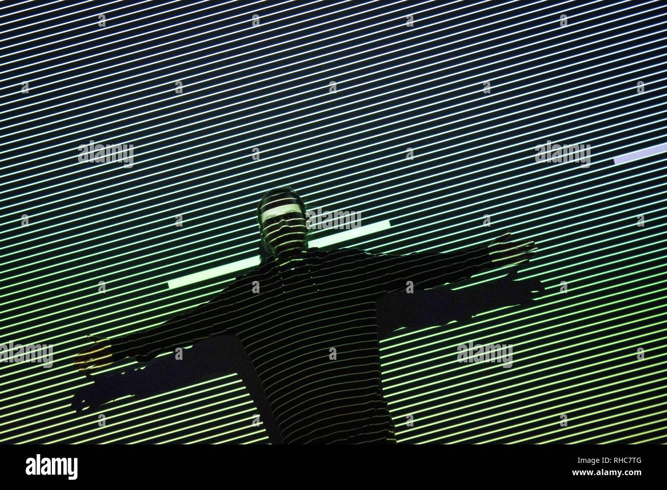Athens, Greece. 1st Feb, 2019. A visitor seen performing with the lights and effect of the Multimedia project Data Flux (12 XGA version) by Japanese artist Ryoji Ikeda at the Onassis Cultural Center in Athens. The Japanese artist presents an installation which challenges the limits of human perception and digital technology. With the precision of a metronome, twelve parallel video projectors synchronize with a minimalist electronic composition, turning numbers and data into the ultimate sensory experience for the visitor. Credit: ZUMA Press, Inc./Alamy Live News - Stock Image