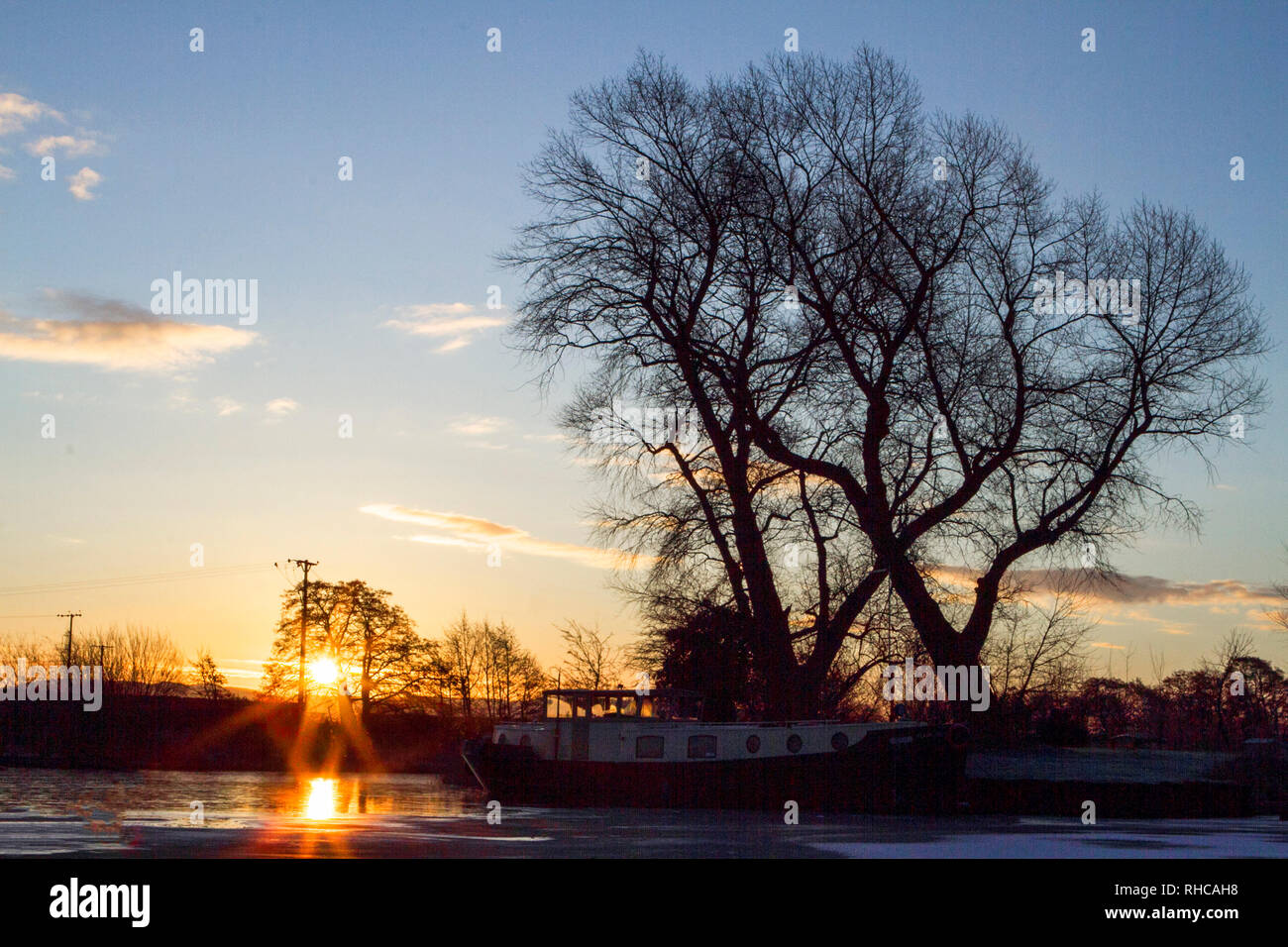 Rufford, West Lancashire, UK. 2nd February 2019. Marina Sunrise. A cool & crisp start to the day as a beautiful morning sunrise cascades over the canal boats moored on the picturesque Rufford Marina in West Lancashire. Credit: Cernan Elias/Alamy Live News - Stock Image