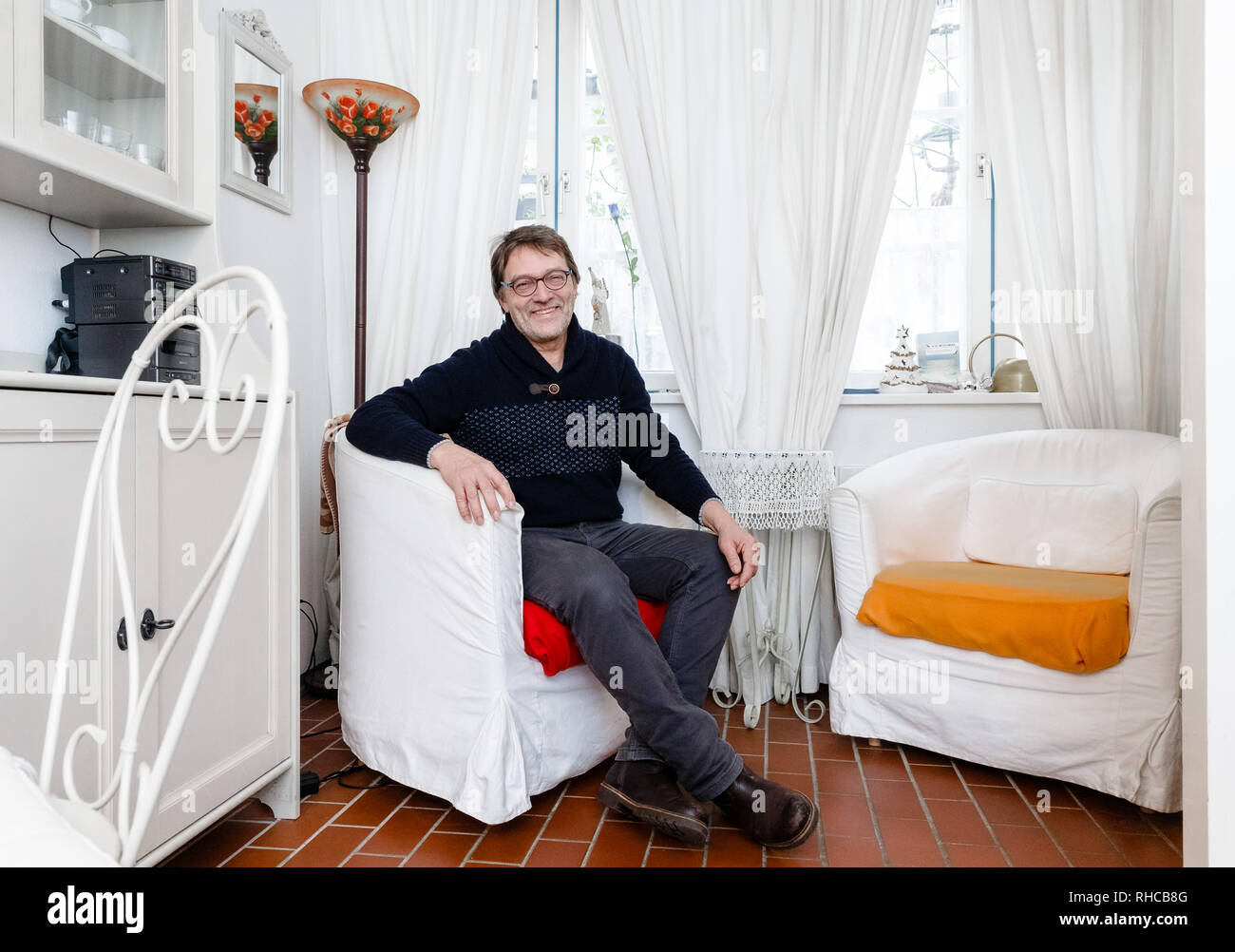 01 February 2019, Schleswig-Holstein, Lübeck: Holiday home owner Wolfgang Seitz sits in his apartment in a historic old building in the centre of Lübeck. Soon the picturesque gang houses in Lübeck will no longer be allowed to be rented to tourists. The homeowners want to sue against the usage ban. They threaten to sell their cottages as second homes to Scandinavians, for example. Photo: Markus Scholz/dpa - Stock Image