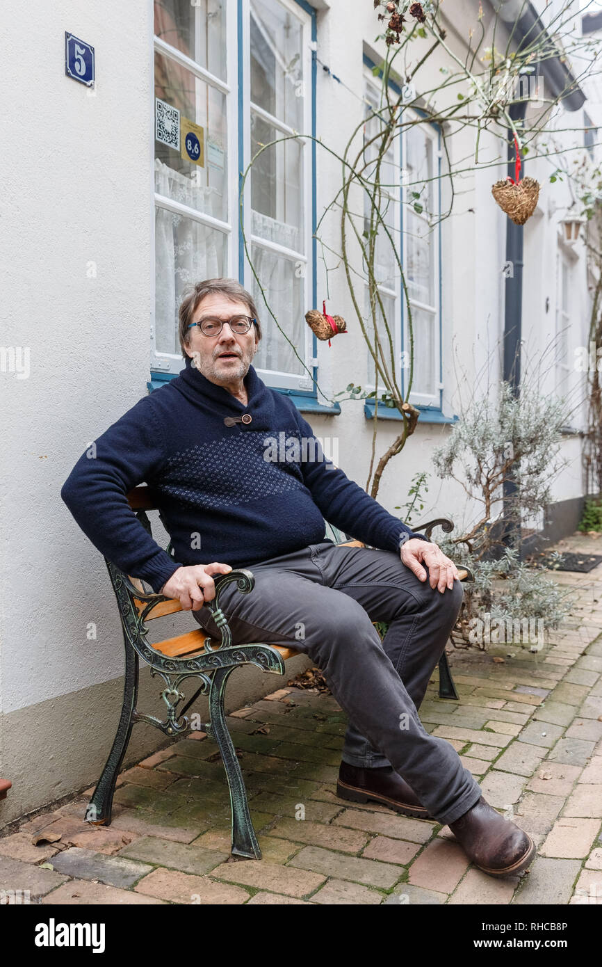 01 February 2019, Schleswig-Holstein, Lübeck: Holiday home owner Wolfgang Seitz sits in front of his apartment in a historic old building in the centre of Lübeck. Soon the picturesque gang houses in Lübeck will no longer be allowed to be rented to tourists. The homeowners want to sue against the usage ban. They threaten to sell their cottages as second homes to Scandinavians, for example. Photo: Markus Scholz/dpa - Stock Image
