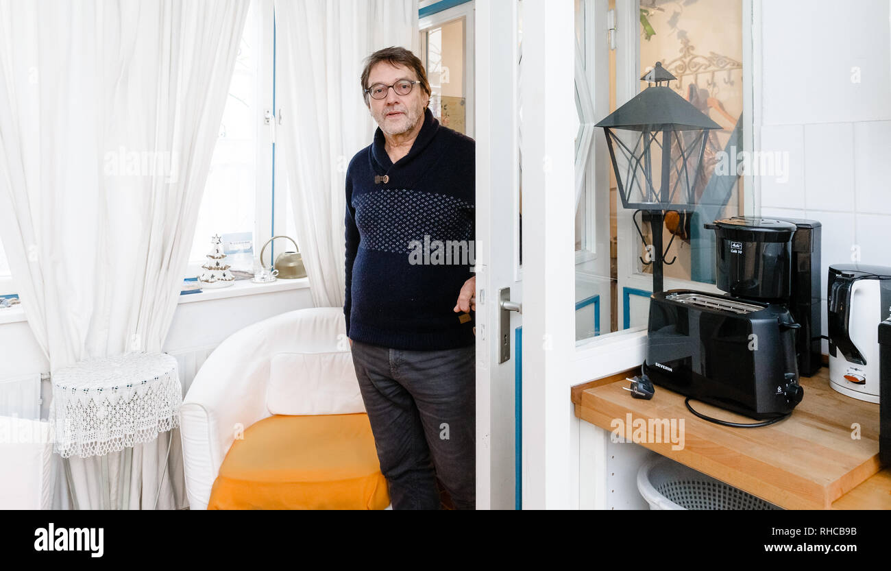 01 February 2019, Schleswig-Holstein, Lübeck: Holiday home owner Wolfgang Seitz stands in his apartment in a historic old building in the centre of Lübeck. Soon the picturesque gang houses in Lübeck will no longer be allowed to be rented to tourists. The homeowners want to sue against the usage ban. They threaten to sell their cottages as second homes to Scandinavians, for example. Photo: Markus Scholz/dpa Stock Photo