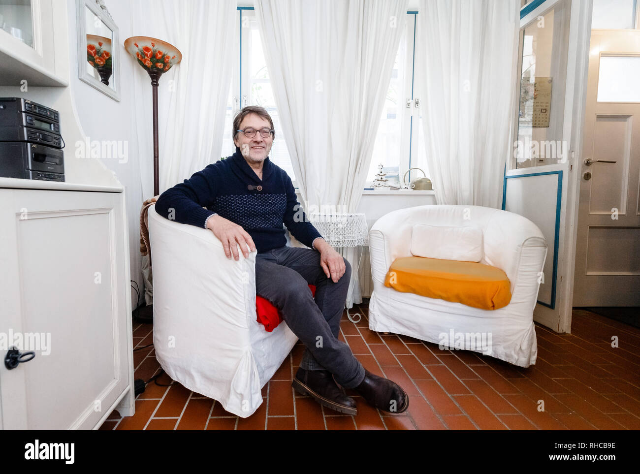 01 February 2019, Schleswig-Holstein, Lübeck: Holiday home owner Wolfgang Seitz sits in his apartment in a historic old building in the centre of Lübeck. Soon the picturesque gang houses in Lübeck will no longer be allowed to be rented to tourists. The homeowners want to sue against the usage ban. They threaten to sell their cottages as second homes to Scandinavians, for example. Photo: Markus Scholz/dpa Stock Photo