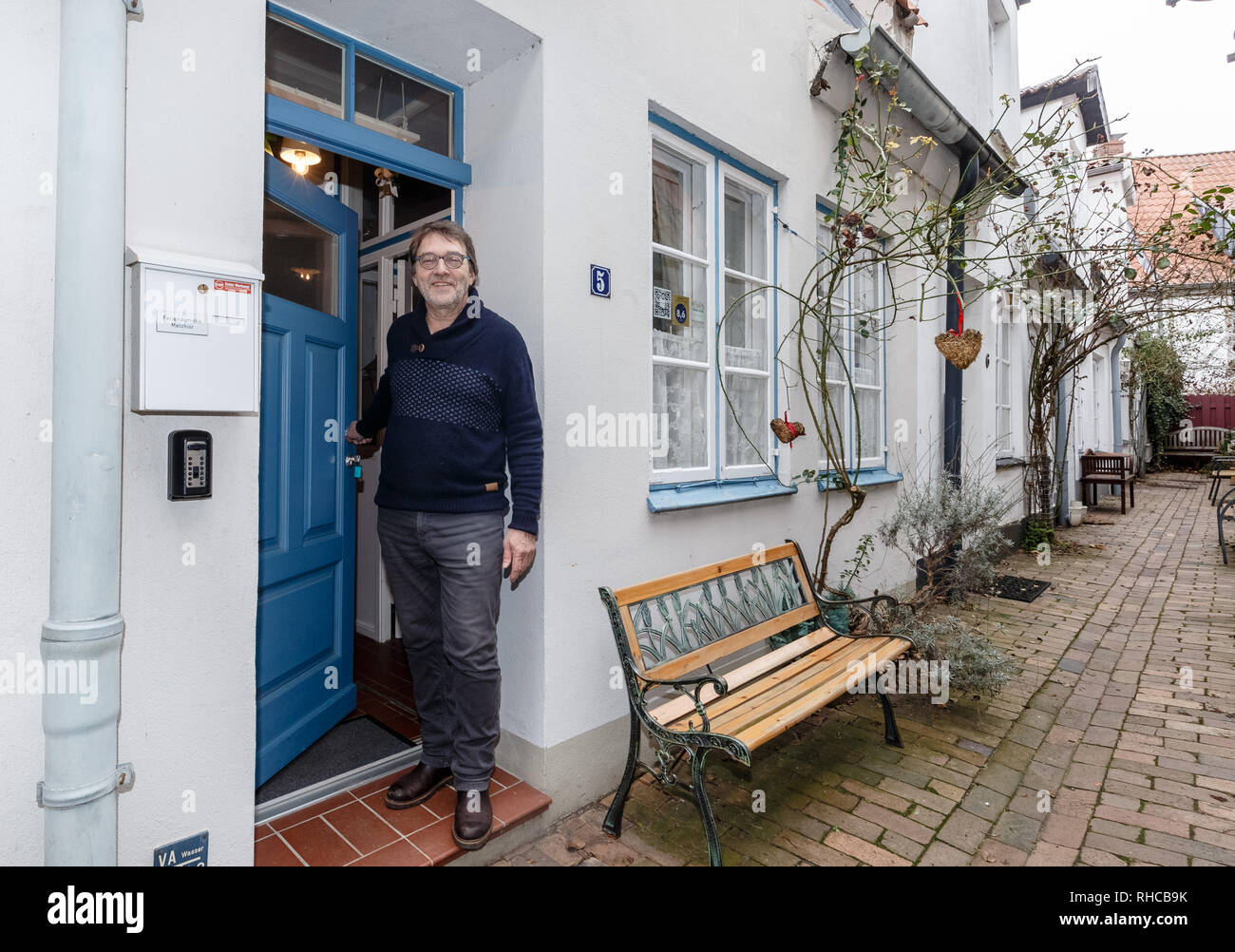 01 February 2019, Schleswig-Holstein, Lübeck: Holiday home owner Wolfgang Seitz stands in front of his apartment in a historic old building in the centre of Lübeck. Soon the picturesque gang houses in Lübeck will no longer be allowed to be rented to tourists. The homeowners want to sue against the usage ban. They threaten to sell their cottages as second homes to Scandinavians, for example. Photo: Markus Scholz/dpa - Stock Image