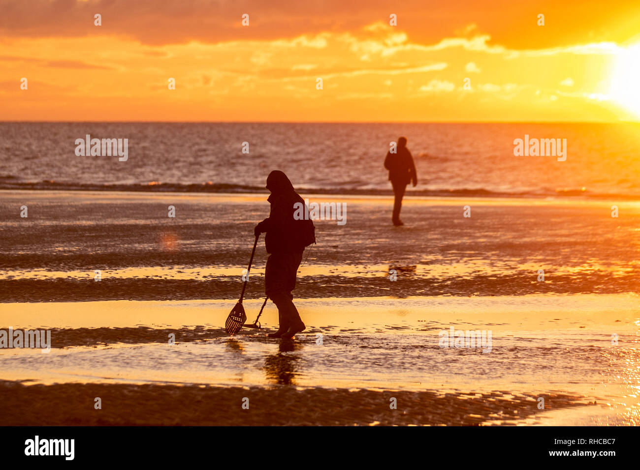 Blackpool, Lancashire. 1st Feb, 2019. UK Weather. Treasure hunting, detector, device, equipment, metal, treasure, ground, hobby, sensor, technology, electronic, find, hunt valuables  at sunset. Metal detectorists in action, scour the shoreline, beach, coast, searching for items of value disturbed by the recent strong tides. Credit: MediaWorldImages/Alamy Live News - Stock Image