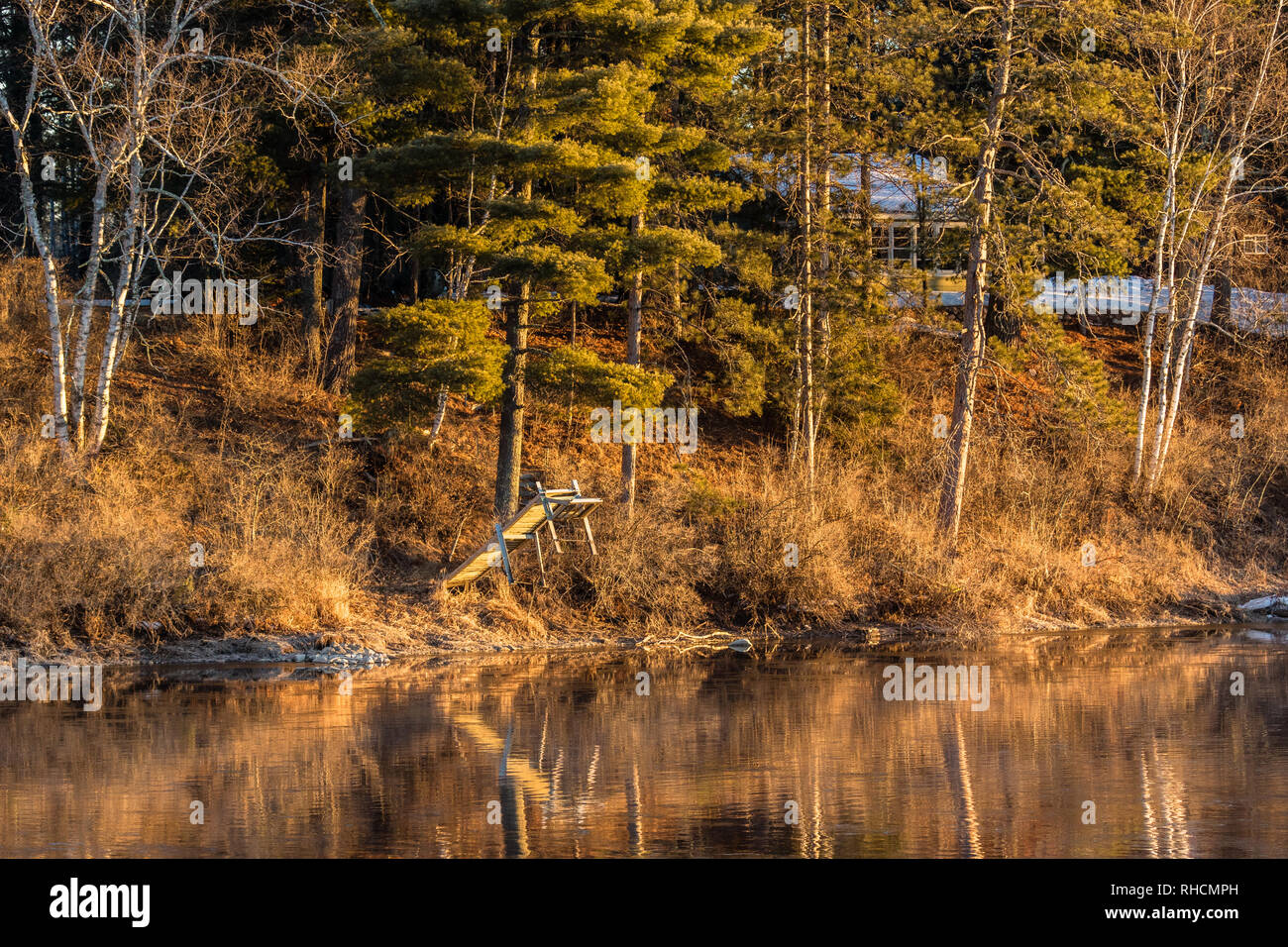 Early morning sunrise on the Chippewa river in northern Wisconsin.  A seasonal resort is the background with some snow still remaining on the ground w - Stock Image