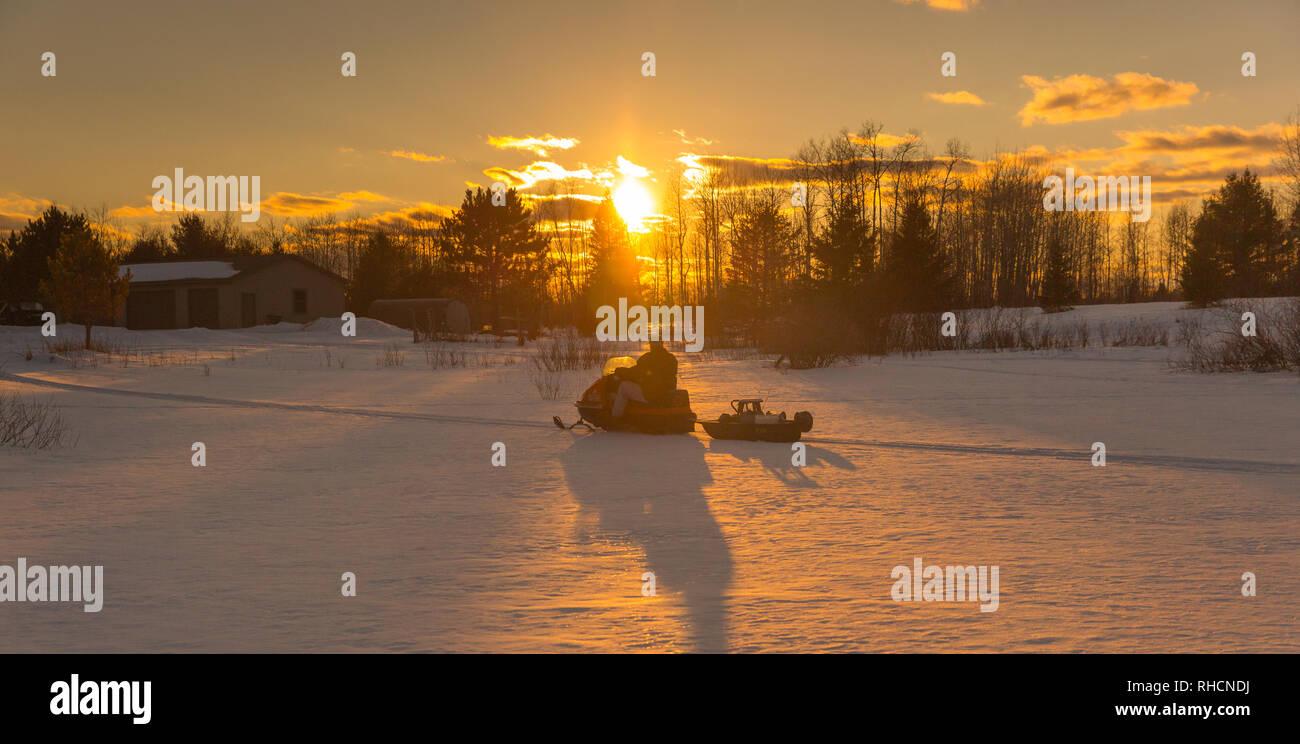 Ice fisherman driving a vintage 1970 AMF Mark V 400 Ski-Daddler snowmobile. - Stock Image