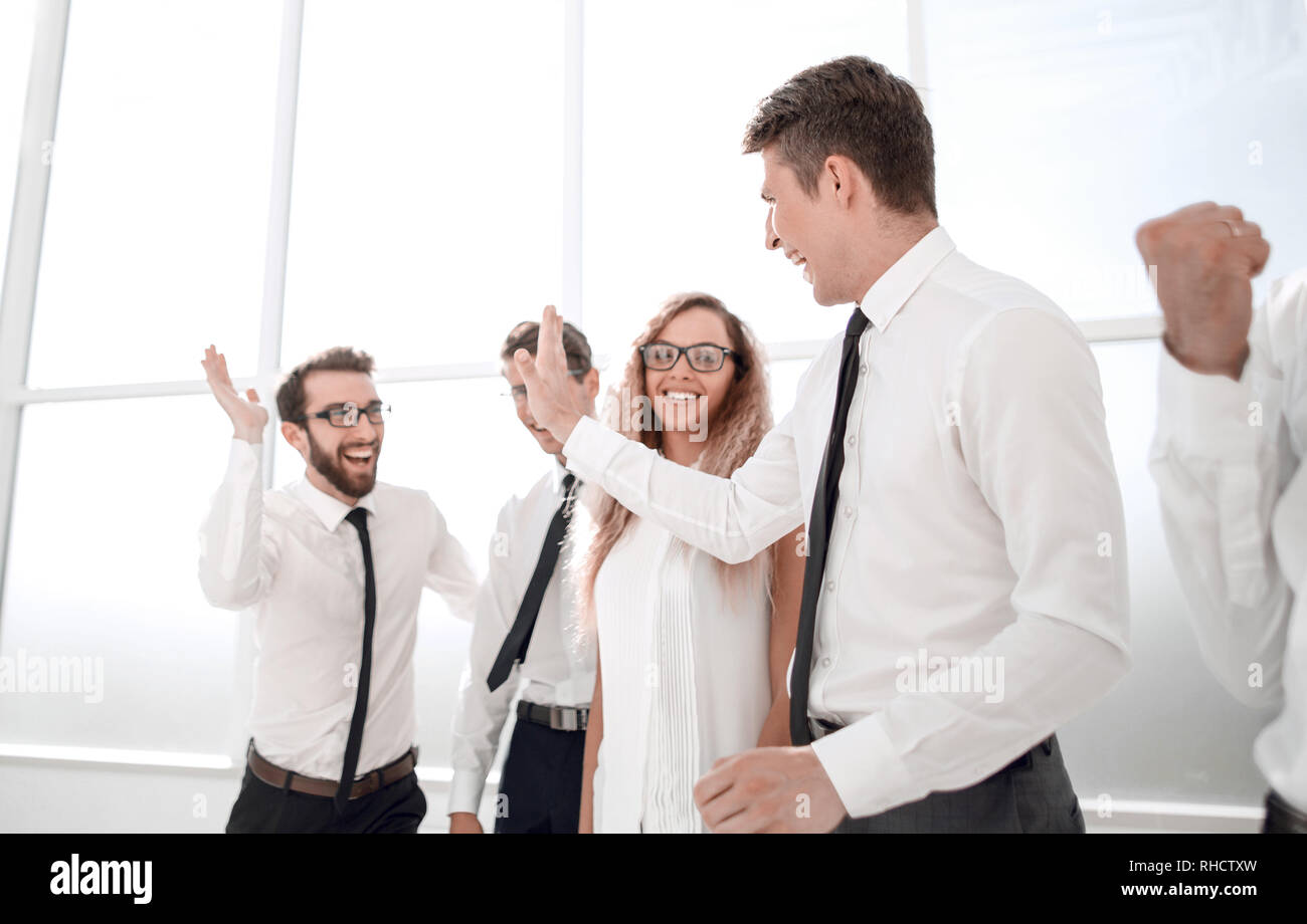 happy employees standing in spacious office - Stock Image
