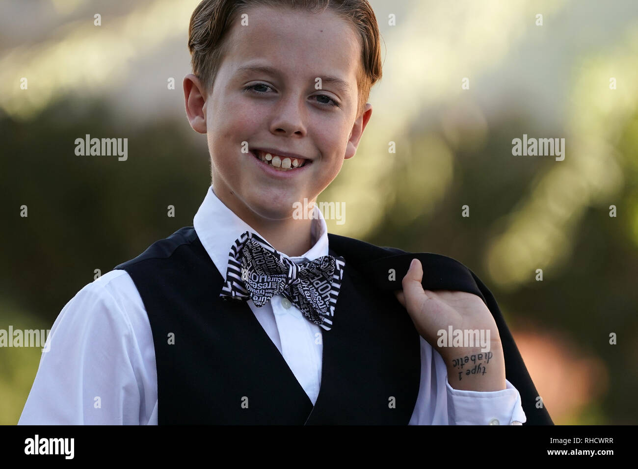 A boy in a suit with a bow tie poses for a portrait. - Stock Image