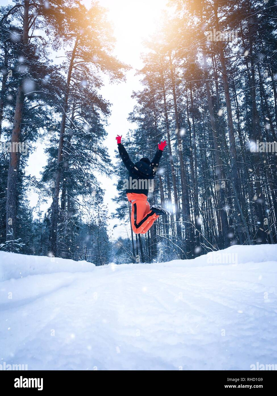 Woman bounces high in the snowy woods - Stock Image