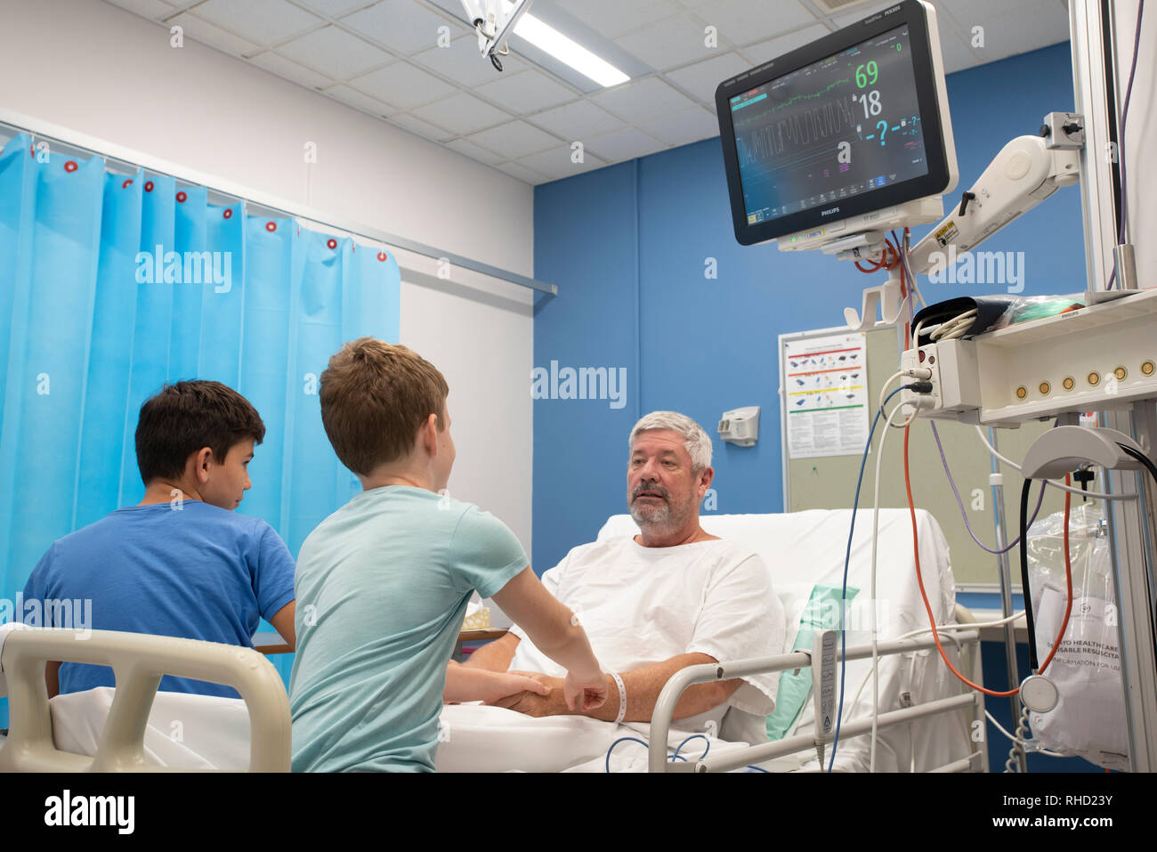 Man in hospital with family around him - Stock Image