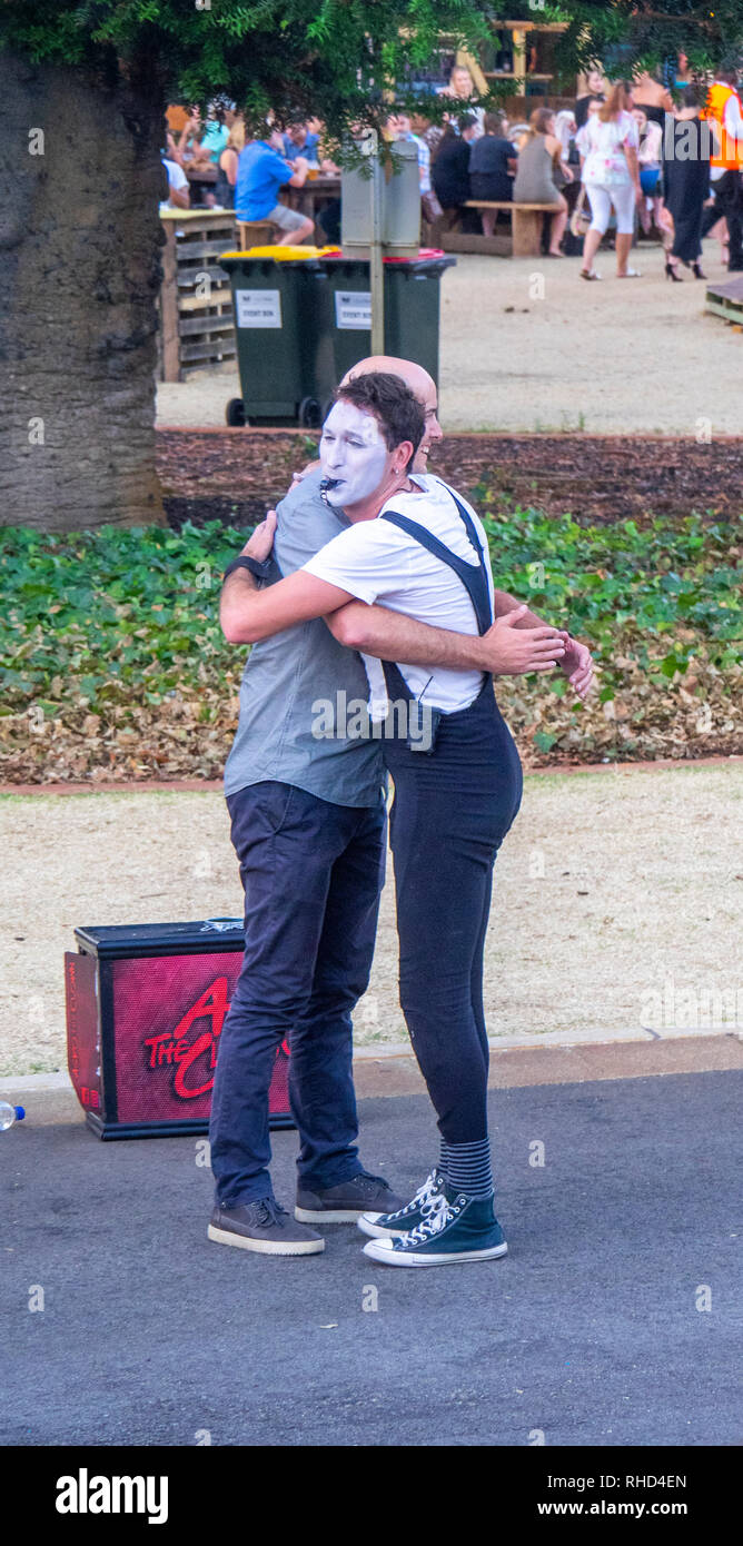 A mime artist hugging a man in front of a crowd at Fringe World Festival Russell Square Northbridge Perth WA Australia. - Stock Image