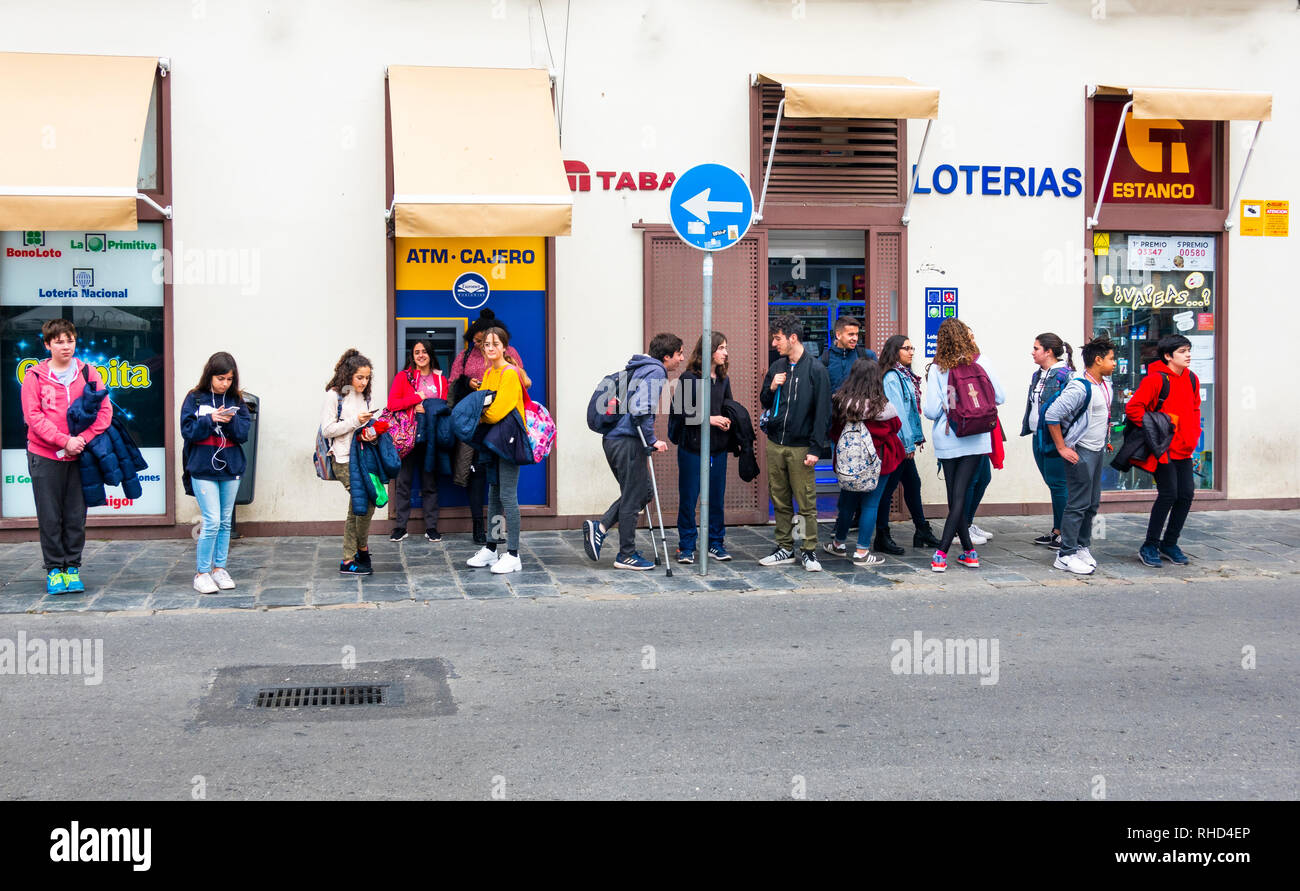 Teenagers after school waiting for a bus in Seville, Spain - Stock Image