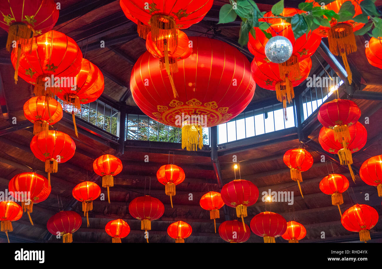 Chinese red lanterns hanging from the roof of a bandstand in