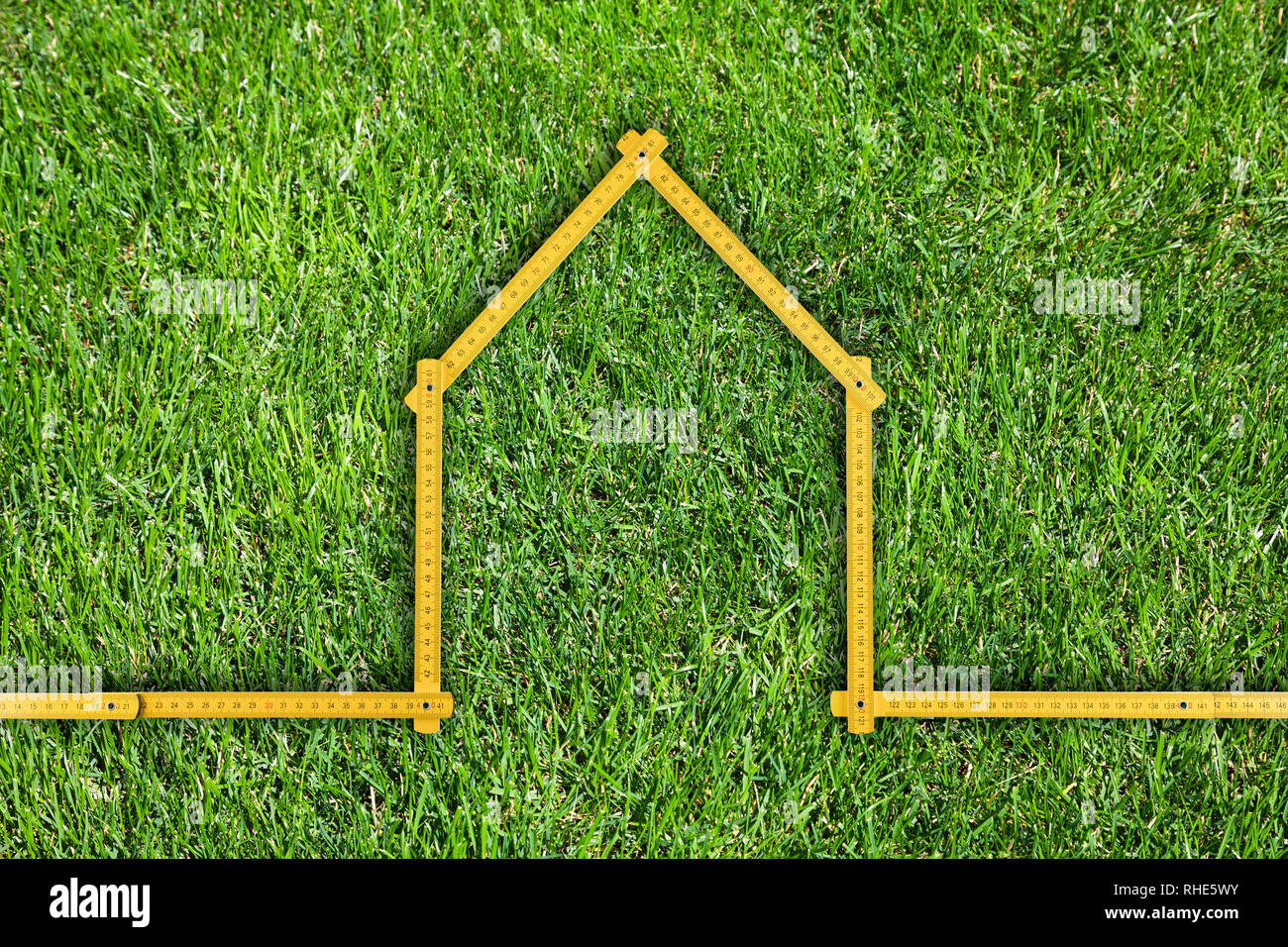 Yellow meter ruler folded as house isolated on green grass - Stock Image