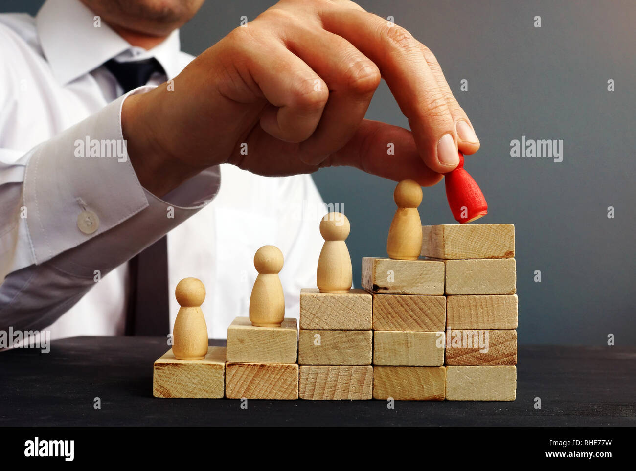 Job Promotion. Manager is holding figurine near career ladder. Worker raises. - Stock Image