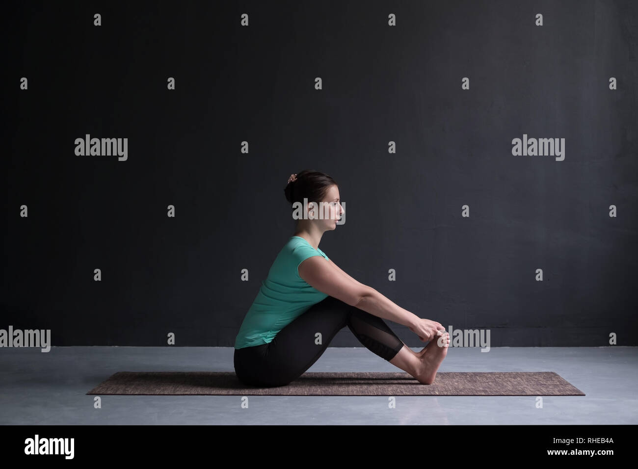 woman practicing yoga, doing Seated forward bend pose, using hands. - Stock Image