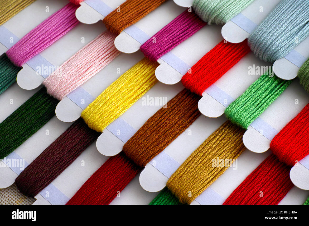 Colored embroidery threads on spools ready for cross stitch. Close-up. - Stock Image