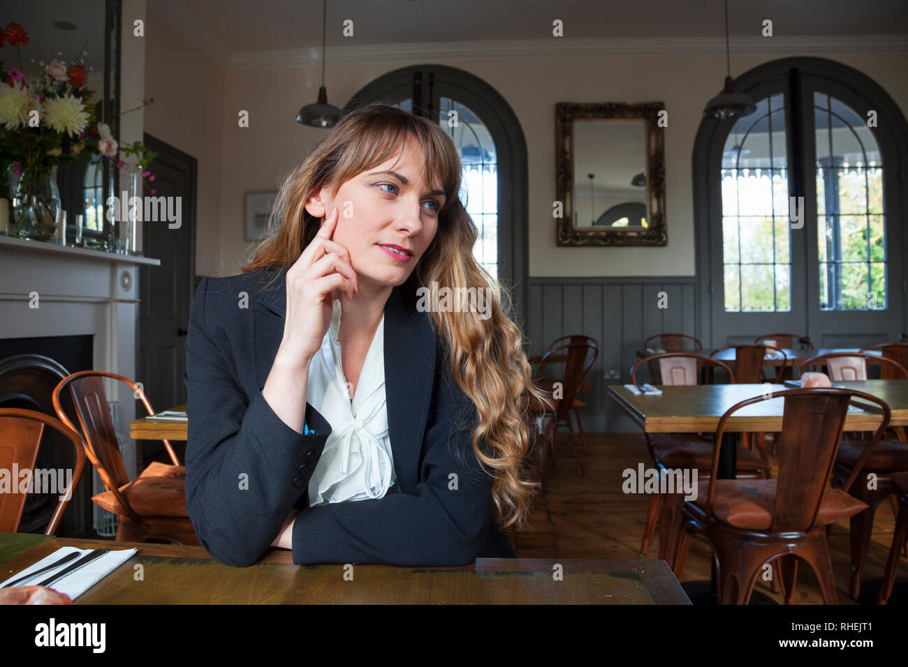 Lady posing for portrait at table in Roydon Station, Restaurant, Essex - Stock Image