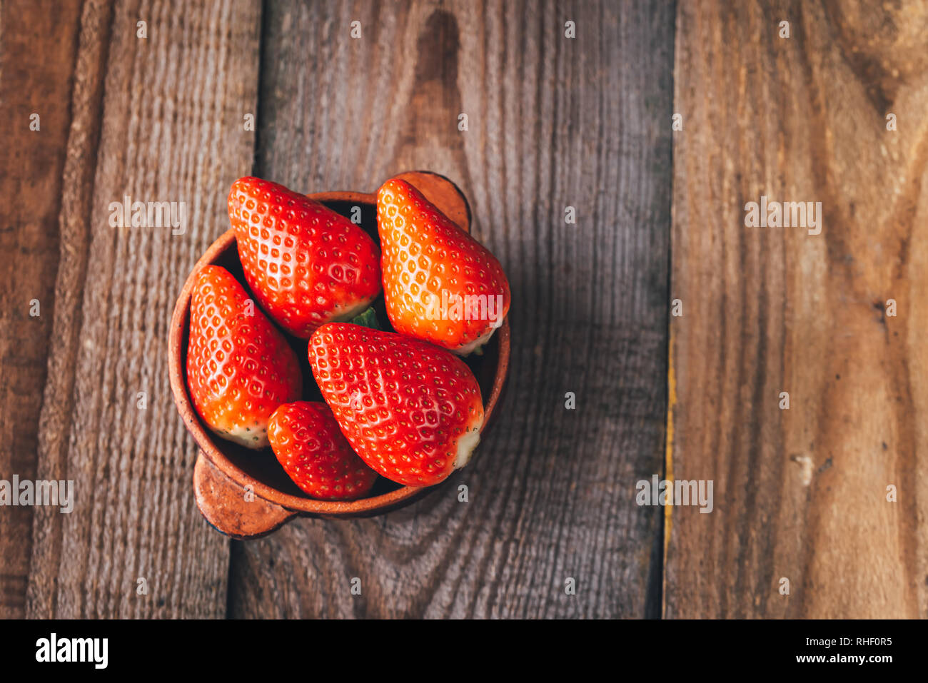 Bowl of fresh strawberries on the wooden table Stock Photo