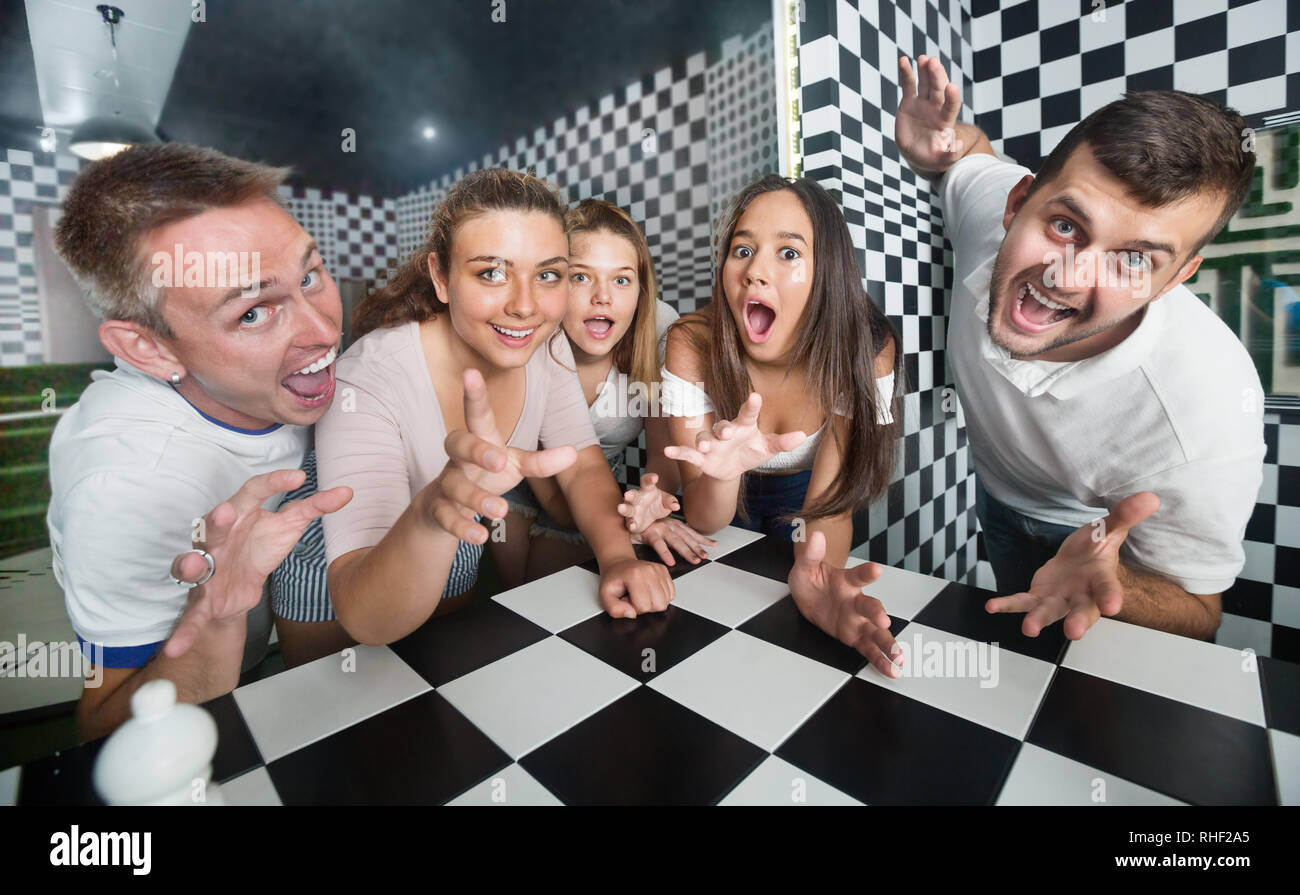 Group of young people having fun in an escape room stylized under chessboard - Stock Image