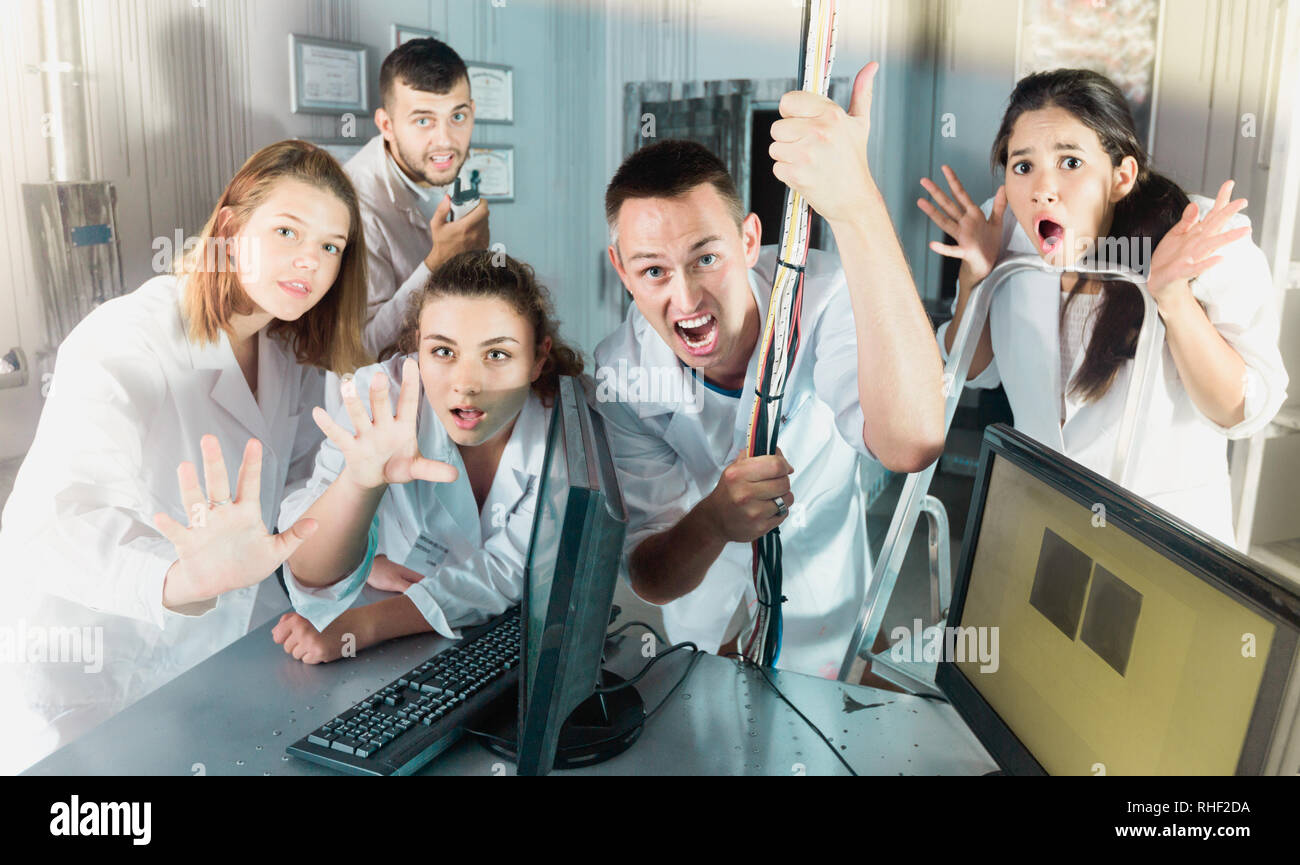 Happy smiling cheerful positive adults laughing and grimacing in quest room-laboratory - Stock Image