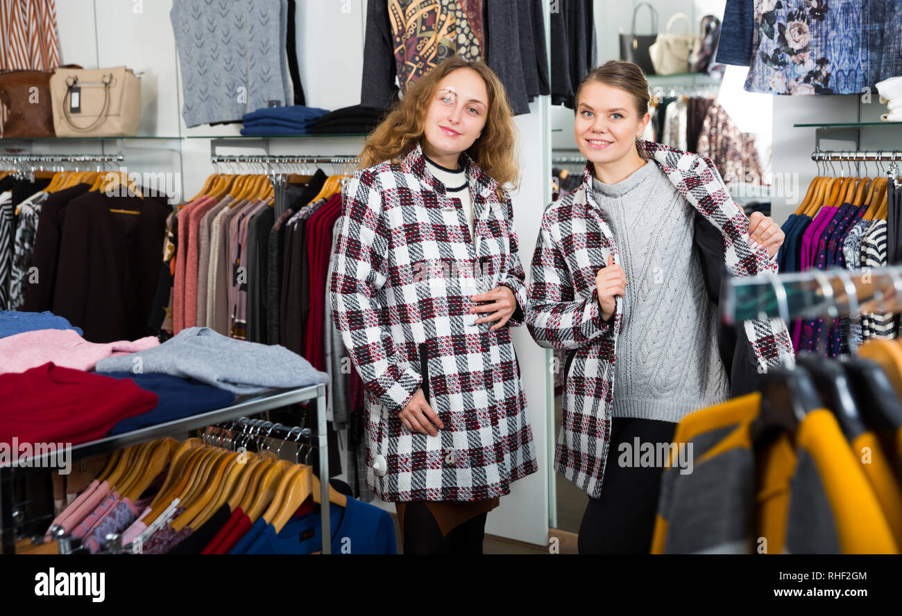 Portrait of two happy female friends posing in new coat in clothing showroom - Stock Image