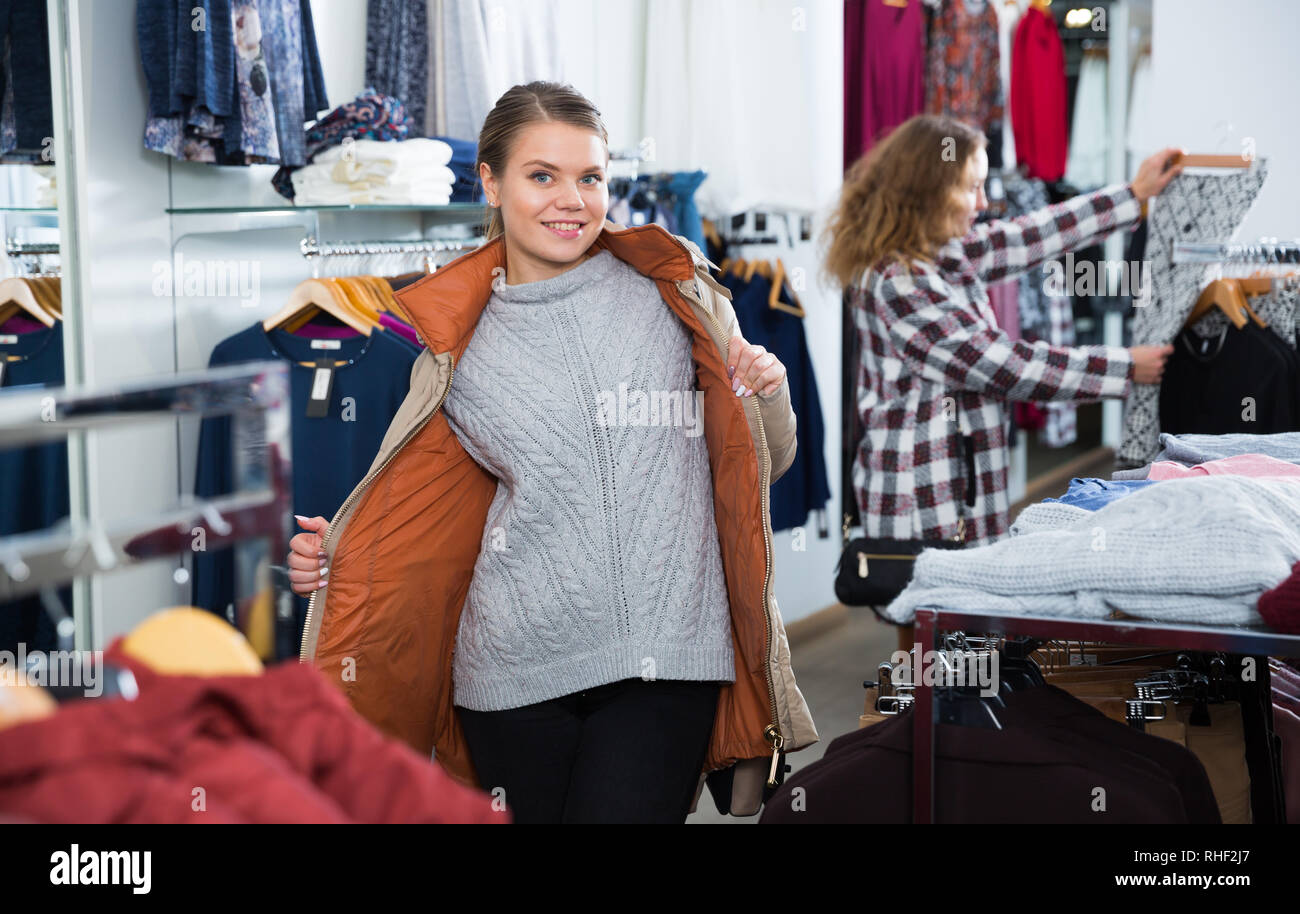 Portrait of happy woman posing wearing coat in clothing store - Stock Image