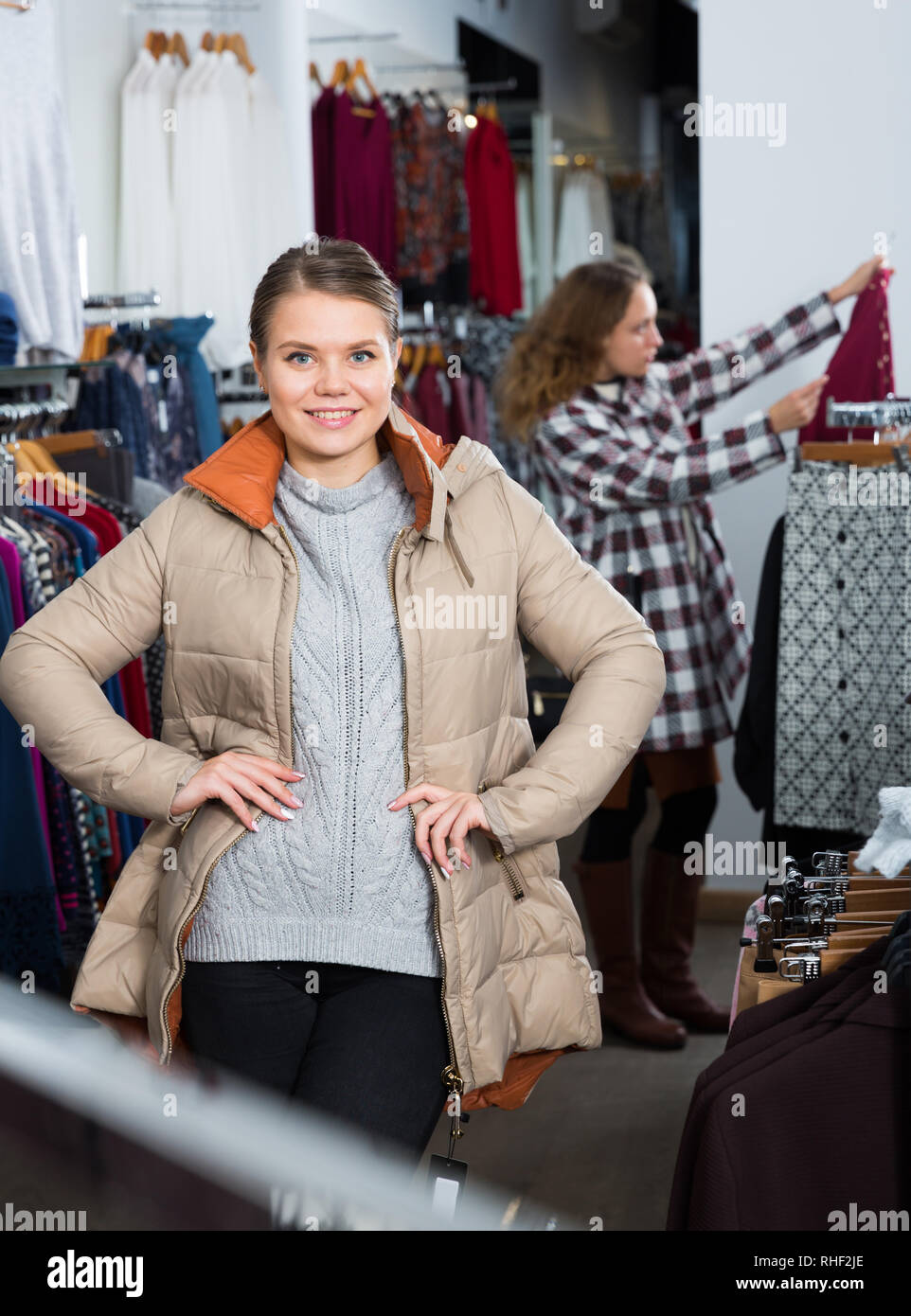Young positive woman standing in overcoat in outerwear clothing boutique - Stock Image
