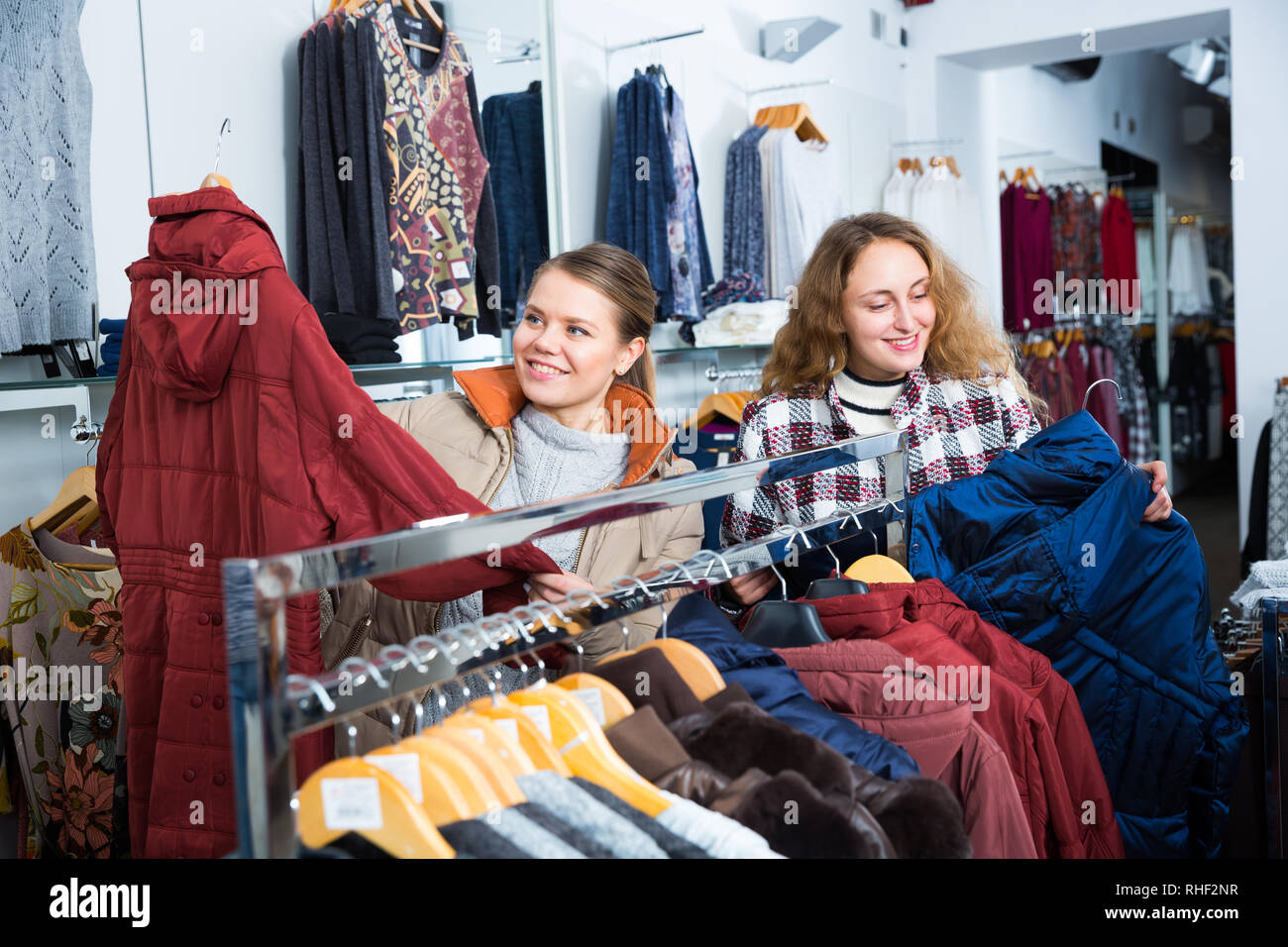 Portrait of two young attractive women choosing new overcoat in clothing store - Stock Image