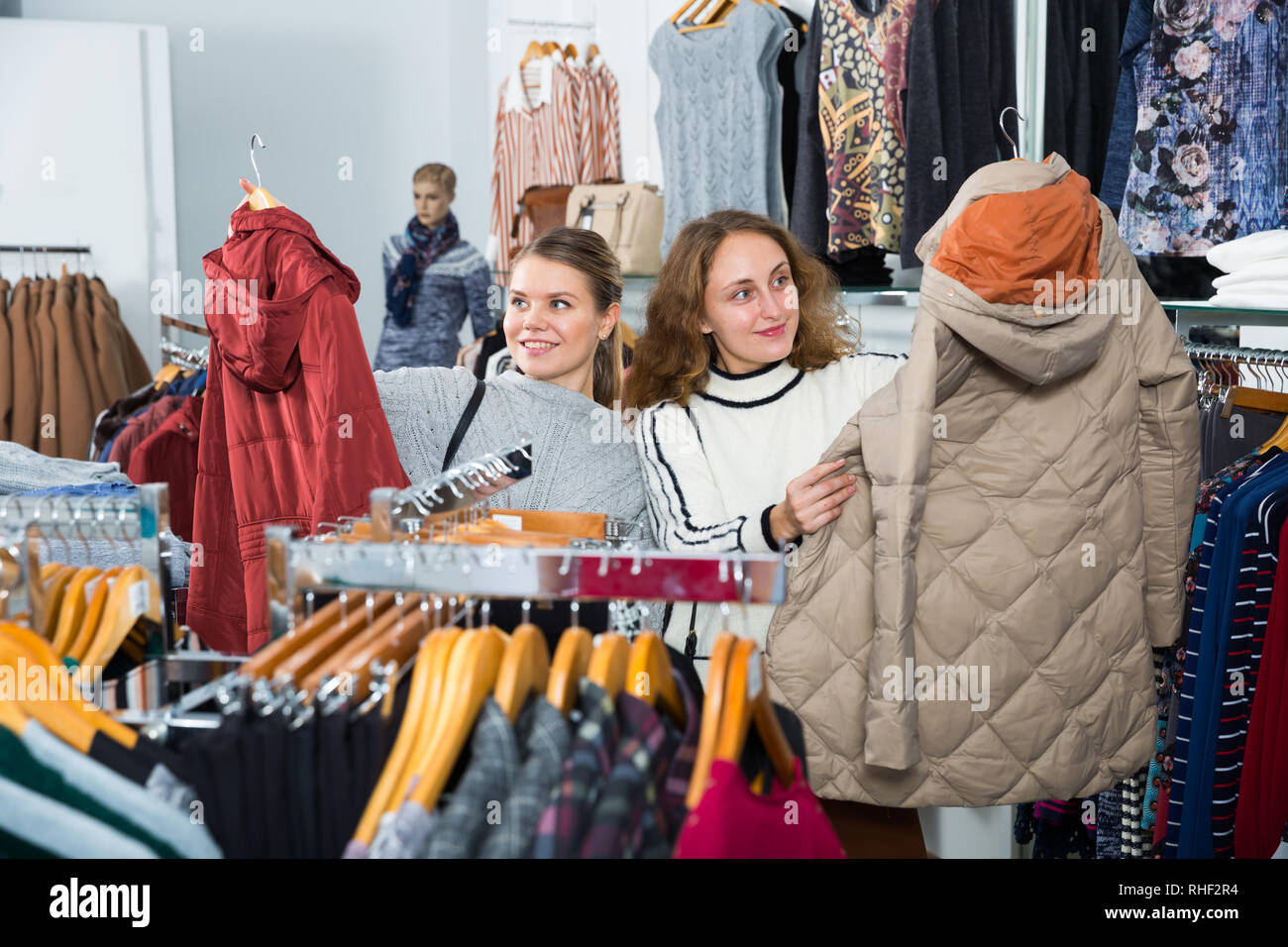 Two young cheerful women shopping in outerwear clothing boutique - Stock Image