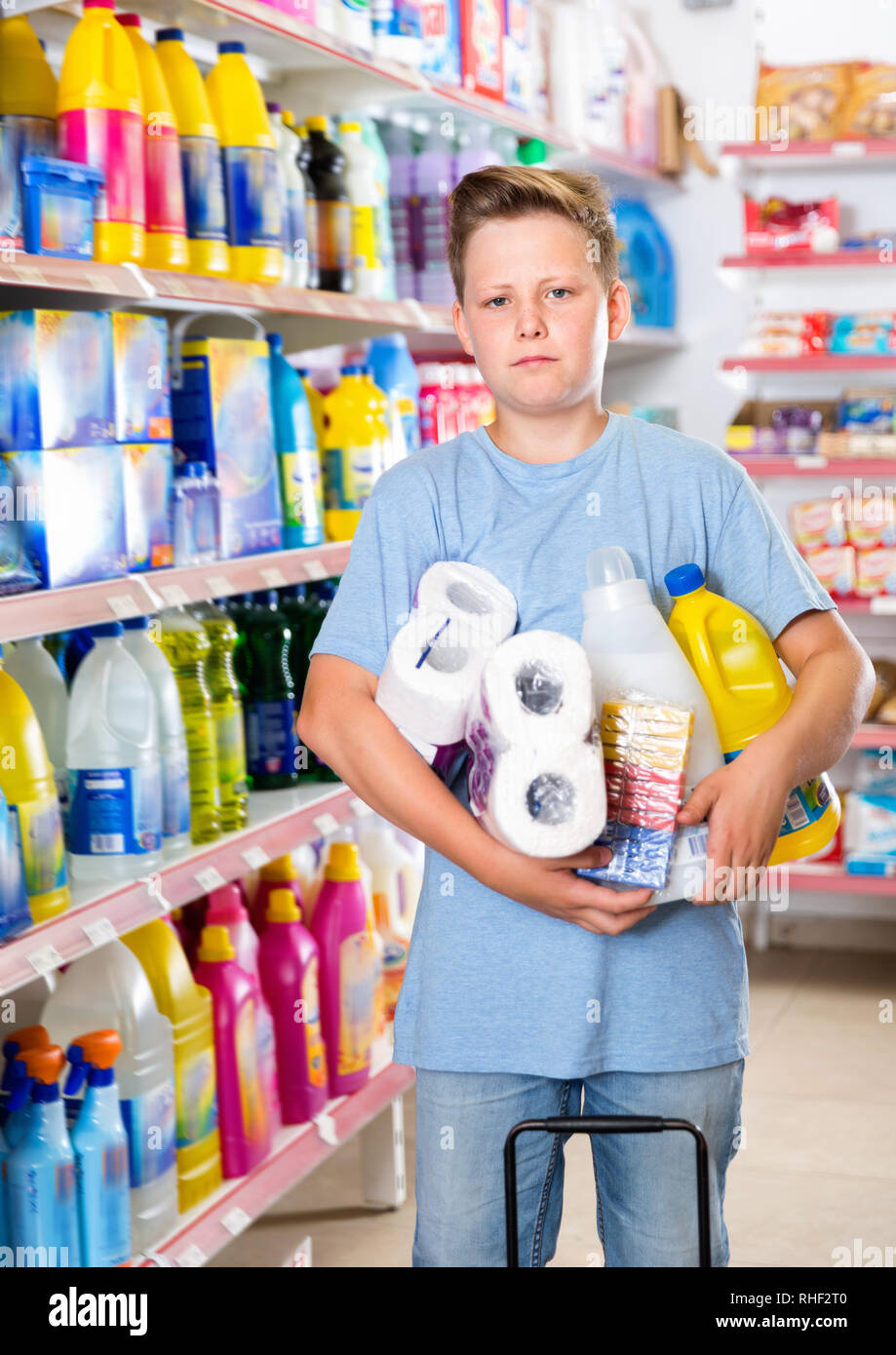 Portrait of happy cheerful positive preteen boy with purchases in supermarket - Stock Image