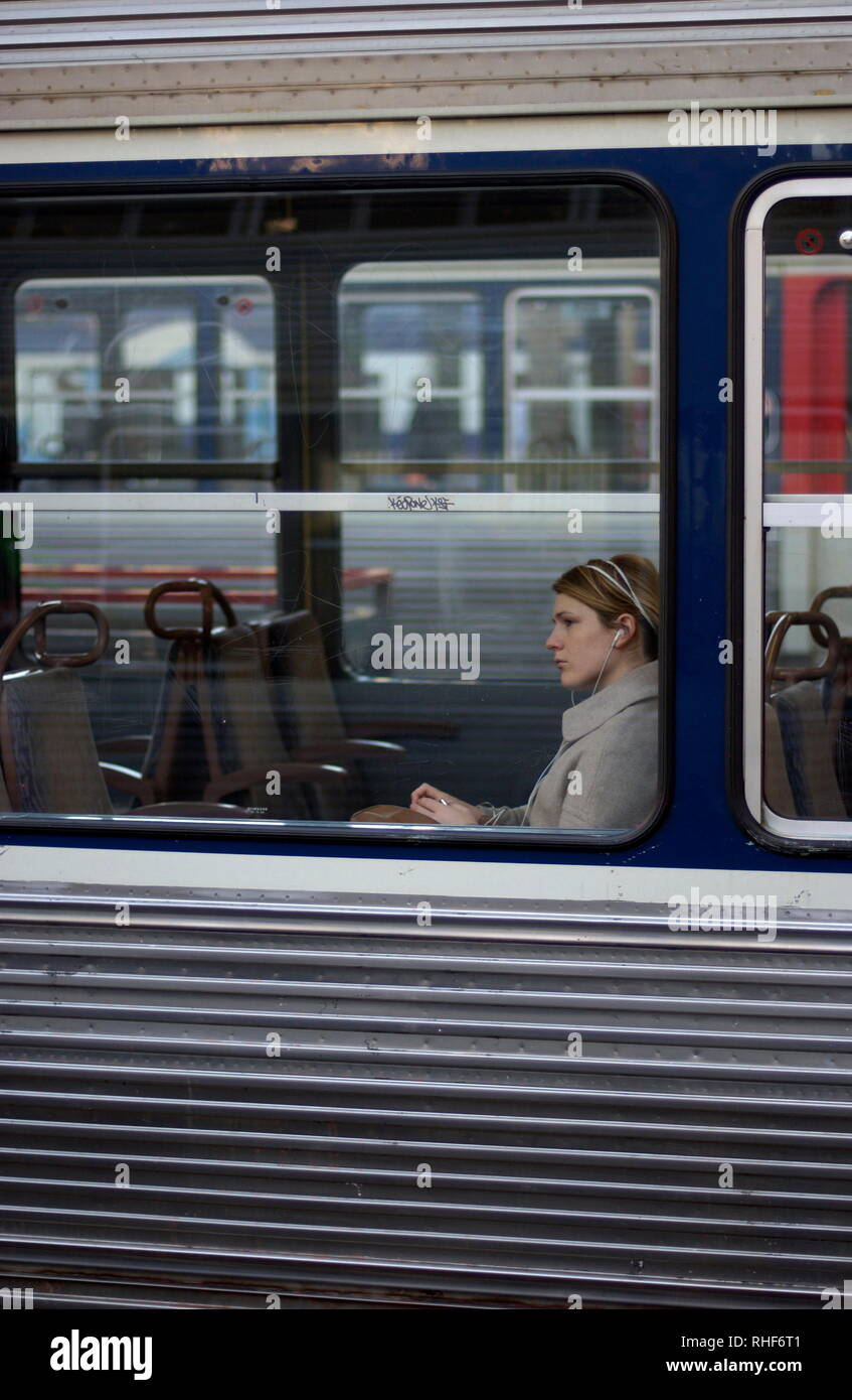 AJAXNETPHOTO. PARIS FRANCE. - THE TRAIN WAITING - PASSENGER WITH HEADPHONES IN A TRAIN WAITING TO DEPART FROM GARE ST.LAZARE. PHOTO;JONATHAN EASTLAND/AJAX REF:D82712_1833 - Stock Image