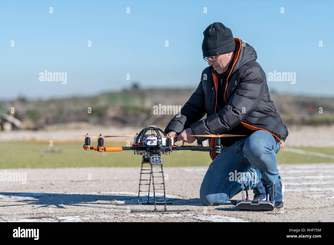 Remote pilot preparing professional drone before flight - Stock Image