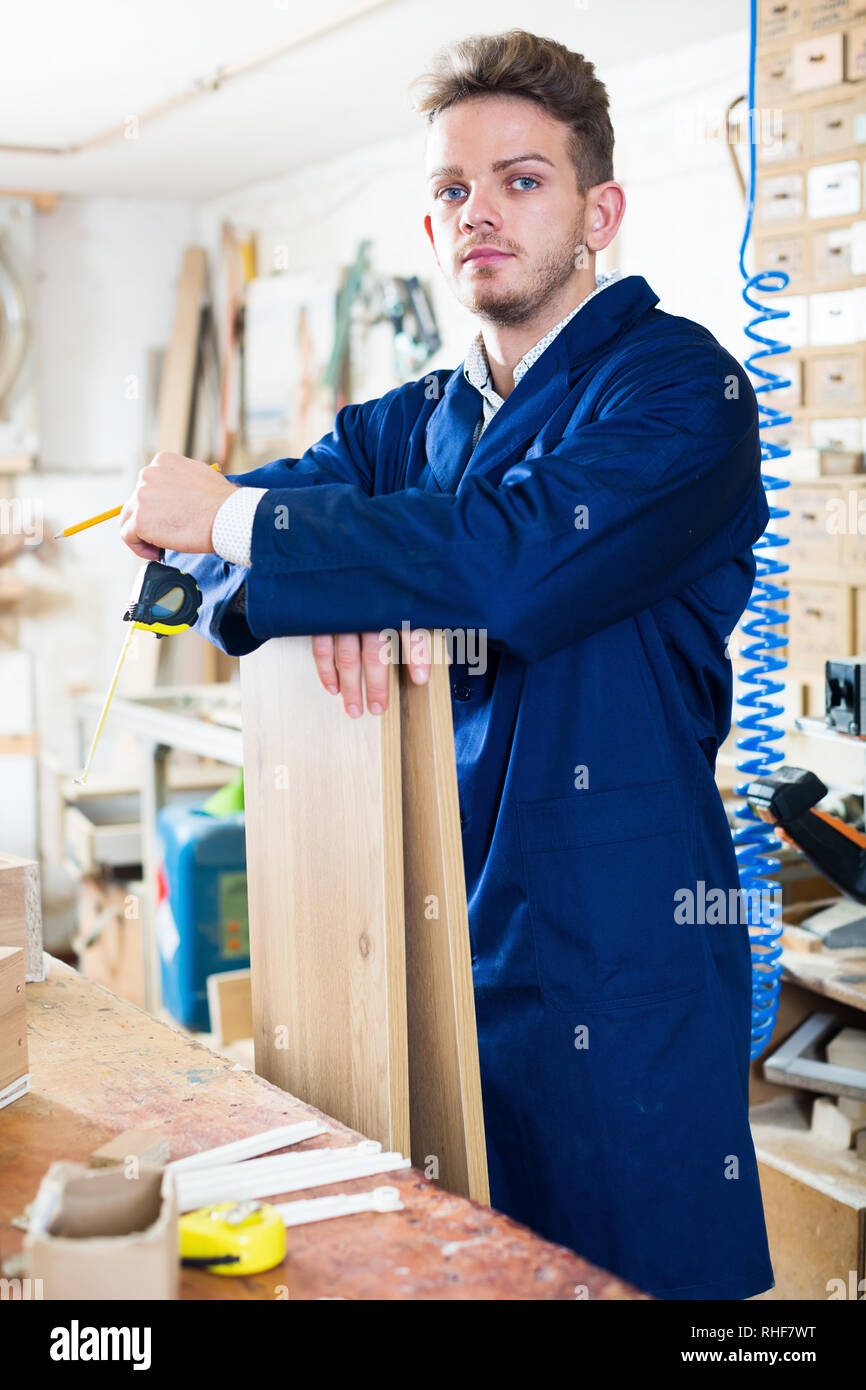 Young smiling woodworker taking measurements for furniture at workshop - Stock Image