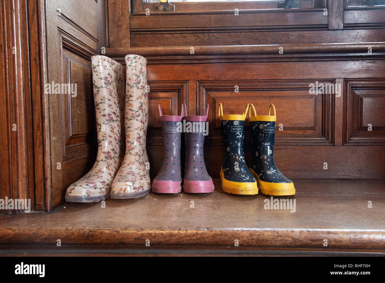 Three pairs of wellington boots - one adult and two children's - in a porch of a house - Stock Image