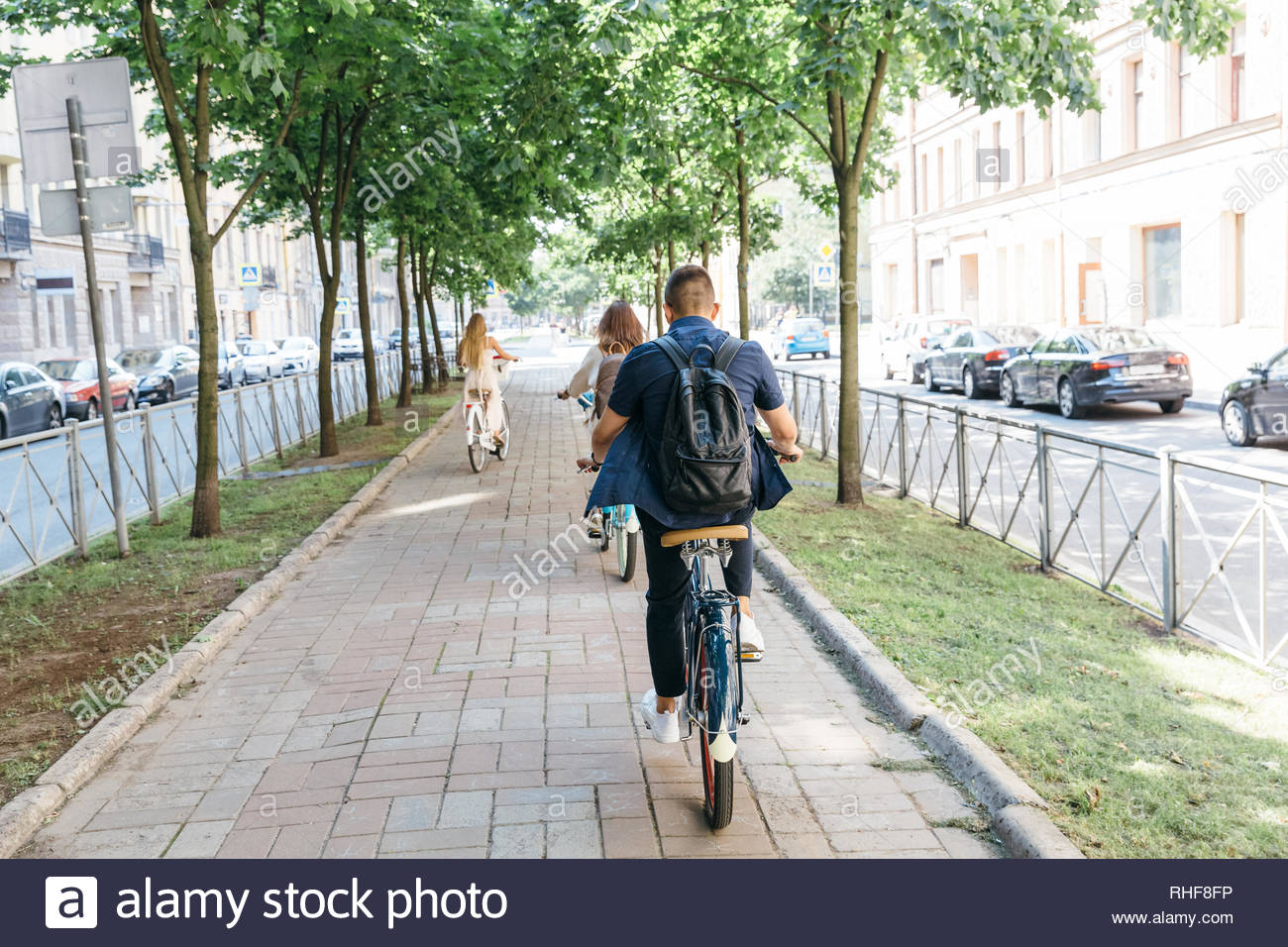 Three people riding bicycles on the boulevard, enjoying cycling on a summer day/ a man and two women ride bikes around the city, go to work/. - Stock Image