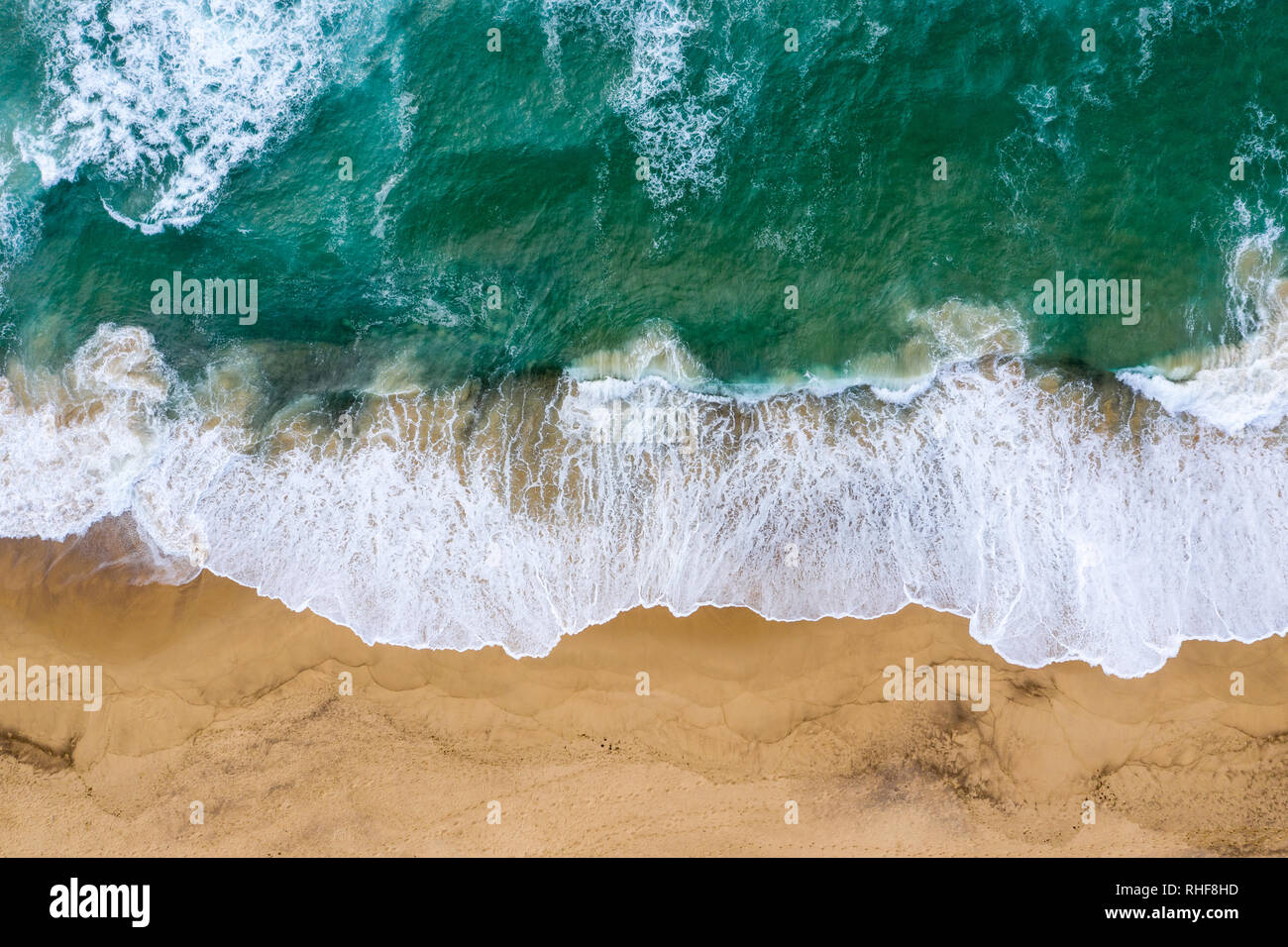 Top down view of the waves crashing onto the sand at Dudley Beach - Newcastle Australia - Stock Image
