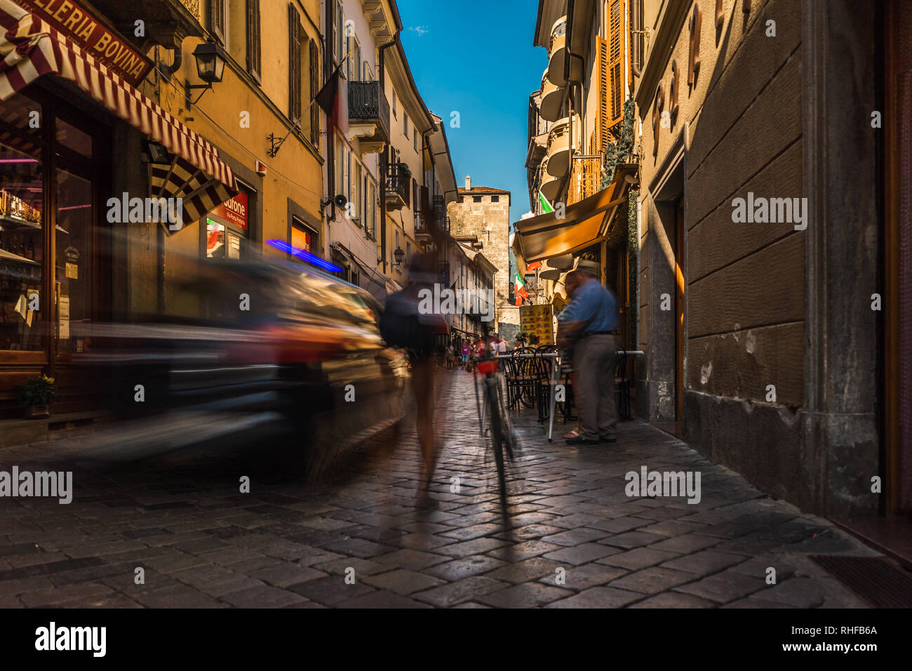 aosta city center street road people walk fast for shopping with a police car intrusion - Stock Image