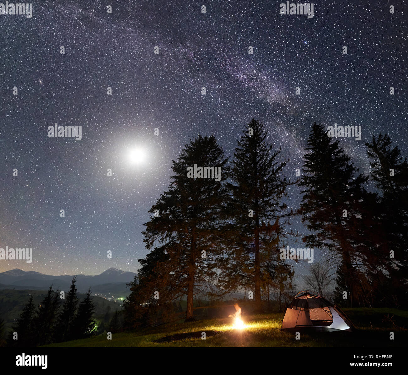 Night camping in mountains  Tourist tent by burning campfire under