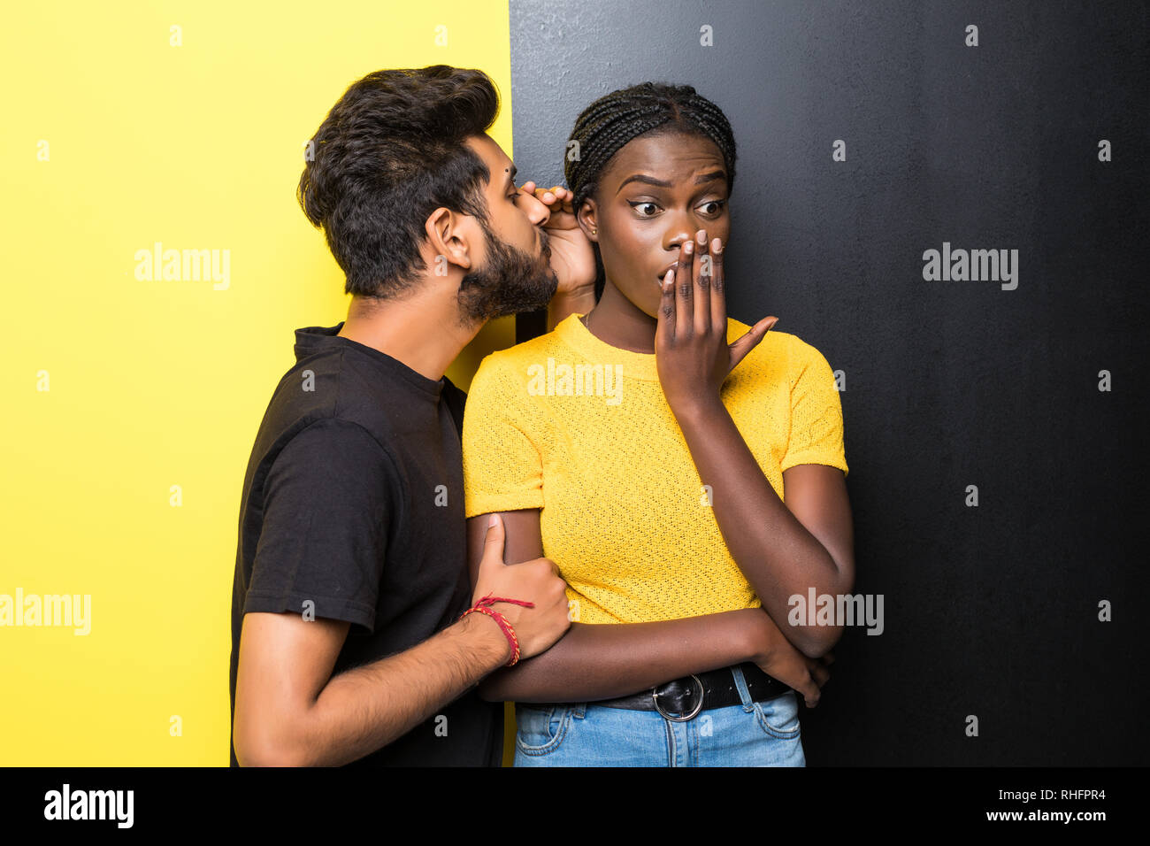 Young happy mixed race couple, indian man whispering secrets african woman standing on different yellow and black background - Stock Image