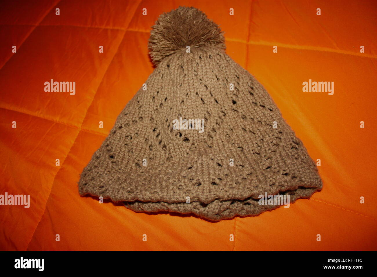 brown knitted wool hat. the background is a bright orange winter duvet Stock Photo