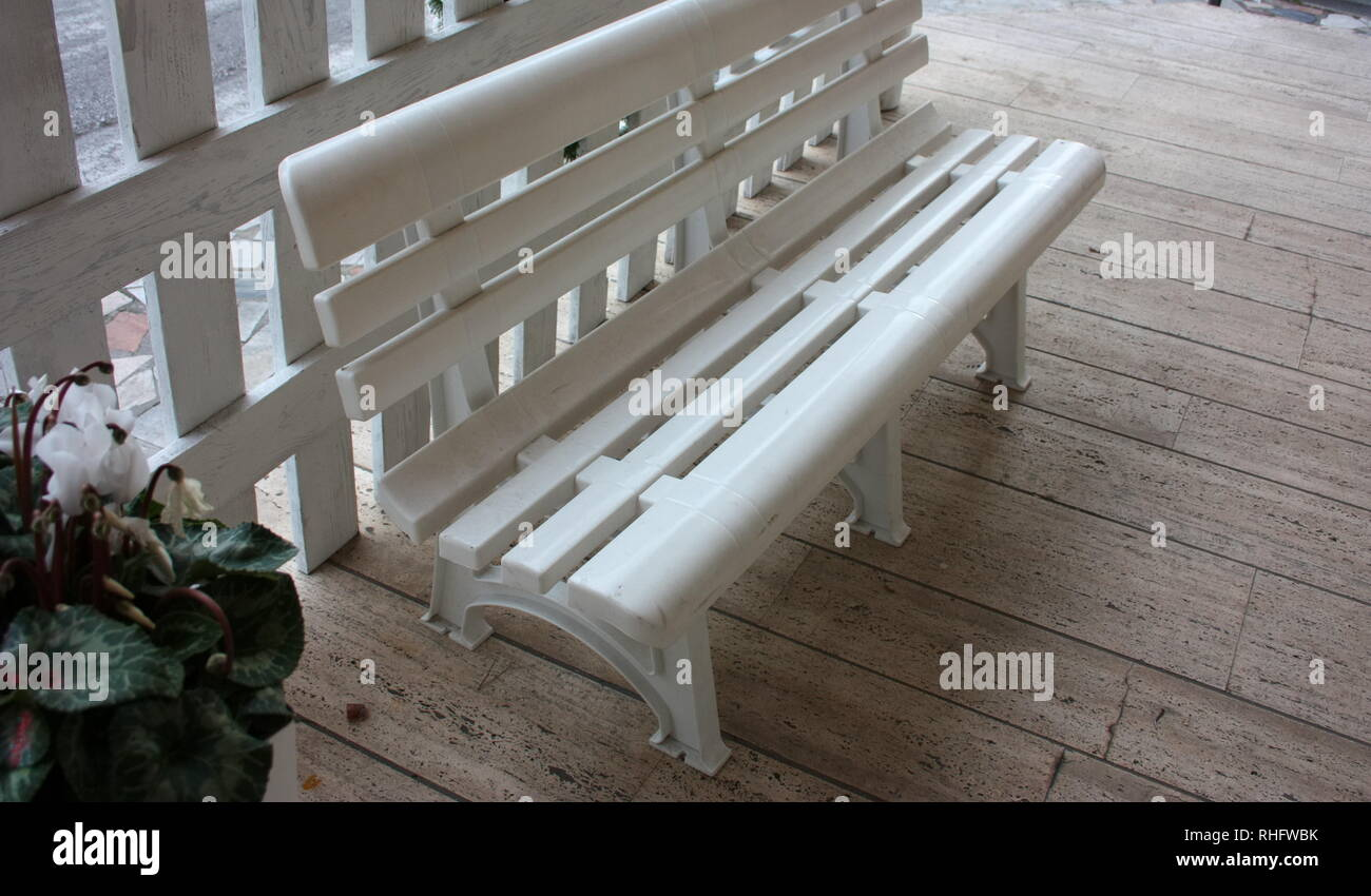 white plastic bench, old, on a paved sidewalk. a vase of flowers nearby. exterior decorations - Stock Image
