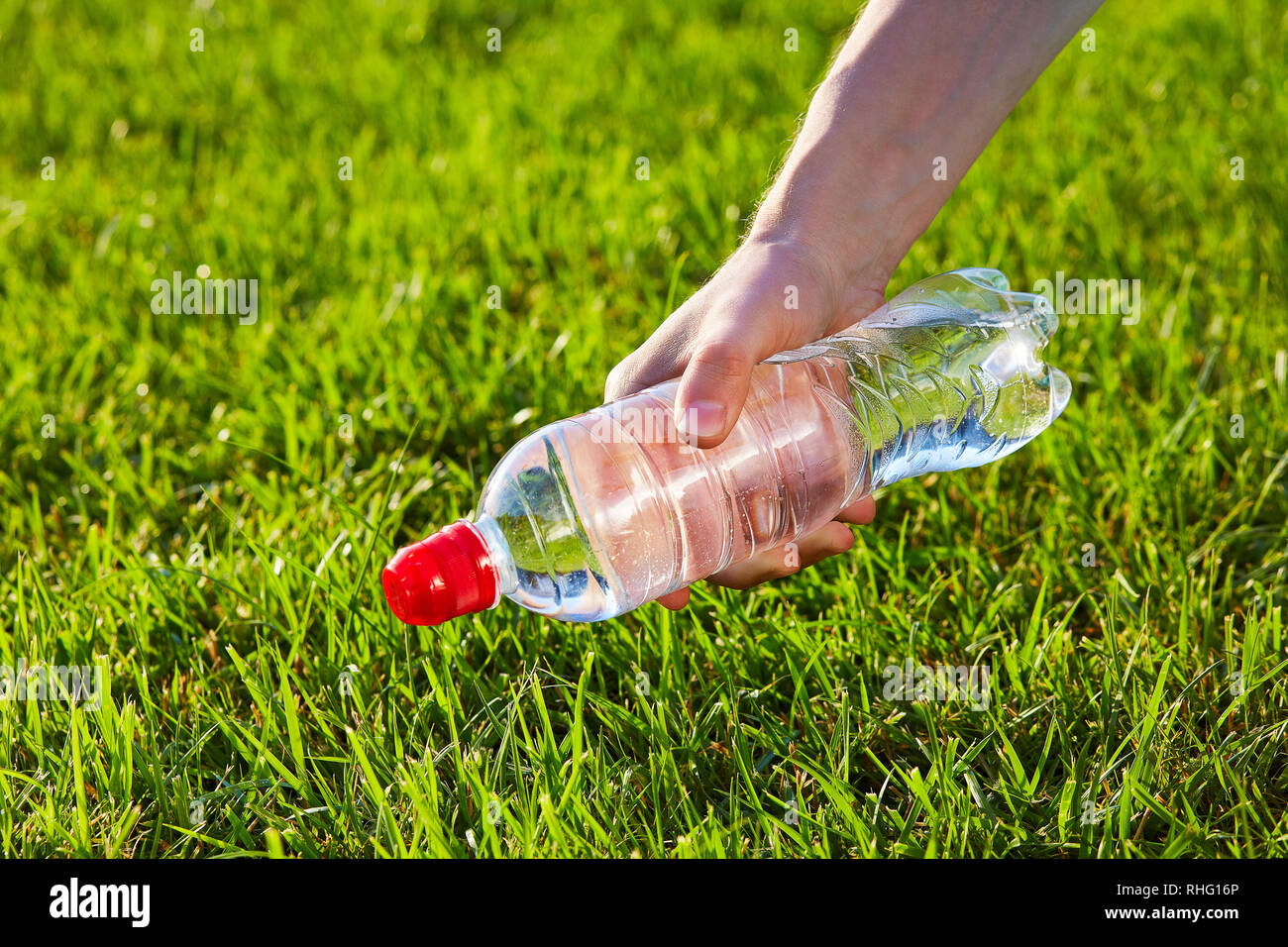 Hand holding a bottle of pure water against green blurred grass background - Stock Image