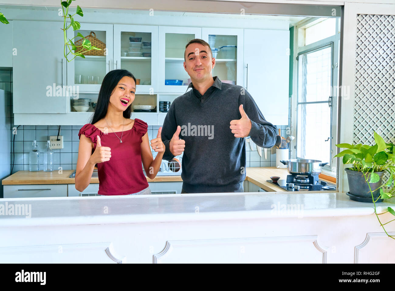 Lovely couple posing - thumbs up and looking at camera - Stock Image
