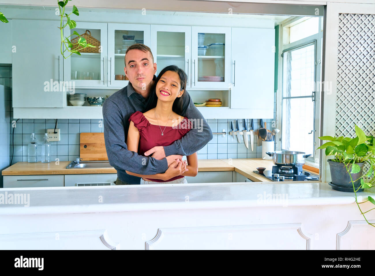 Lovely couple posing - embracing and smiling face of young woman - Stock Image