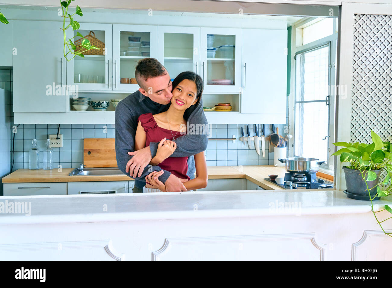 Lovely couple posing - embracing and kissing on cheek - Stock Image