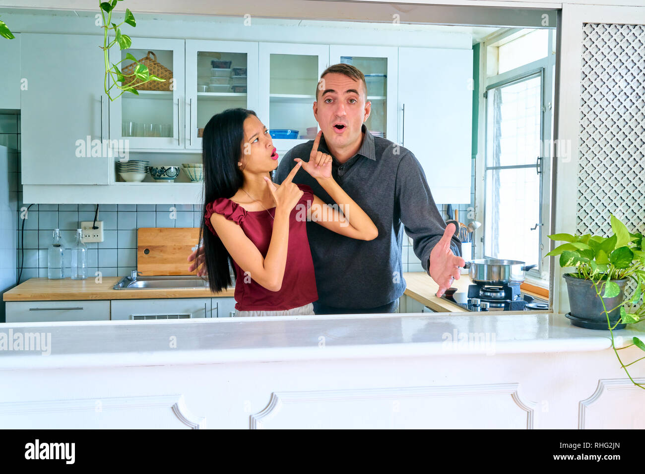Lovely couple posing - pointing to man - Stock Image