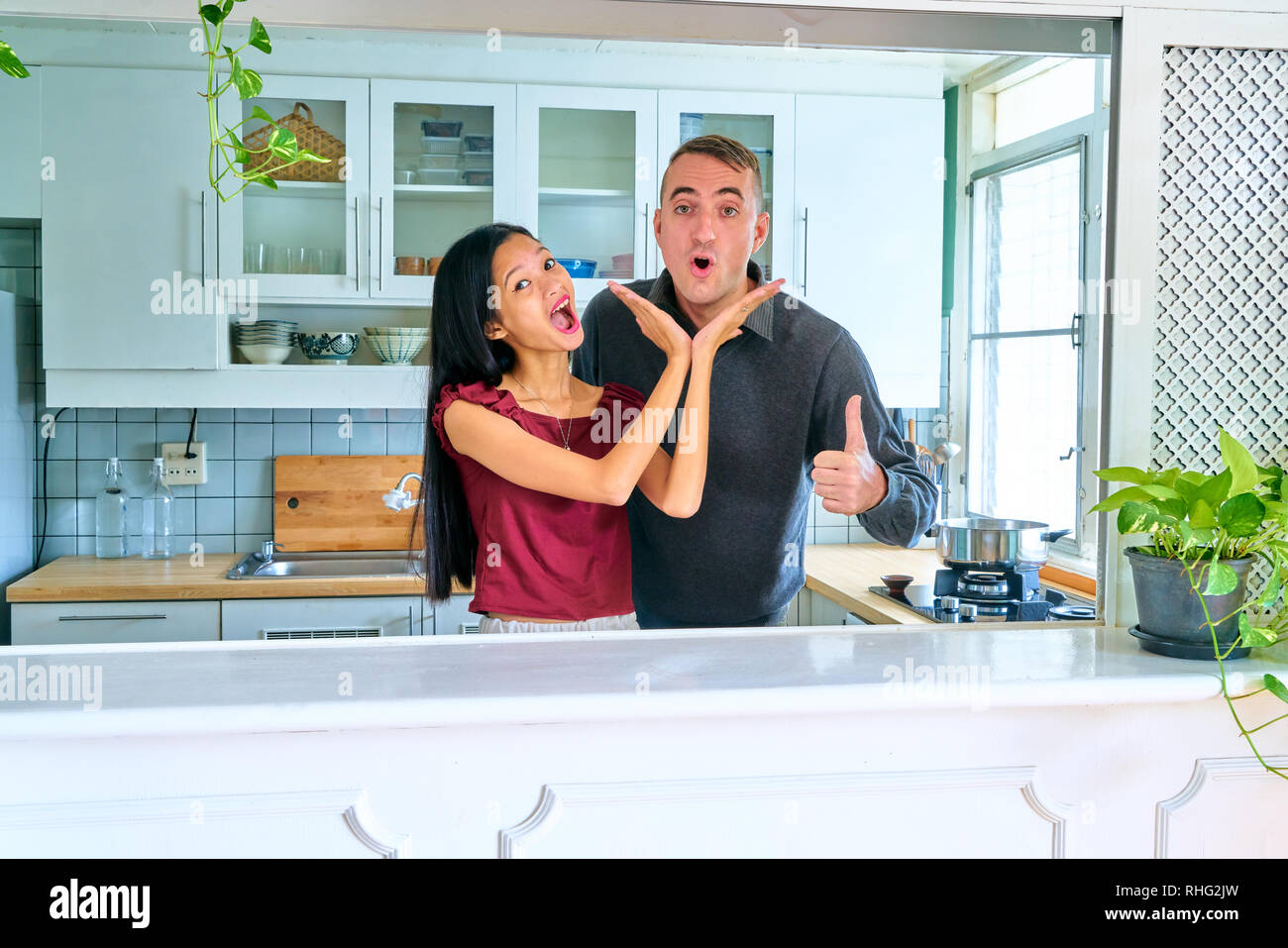 Lovely couple posing - thumbs up gesture and fun moments - Stock Image