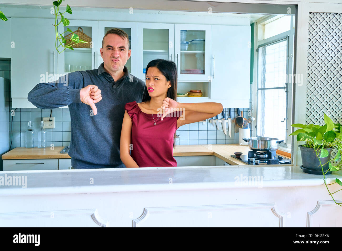 Disappointment couple showing dislike with thumbs down. - Stock Image